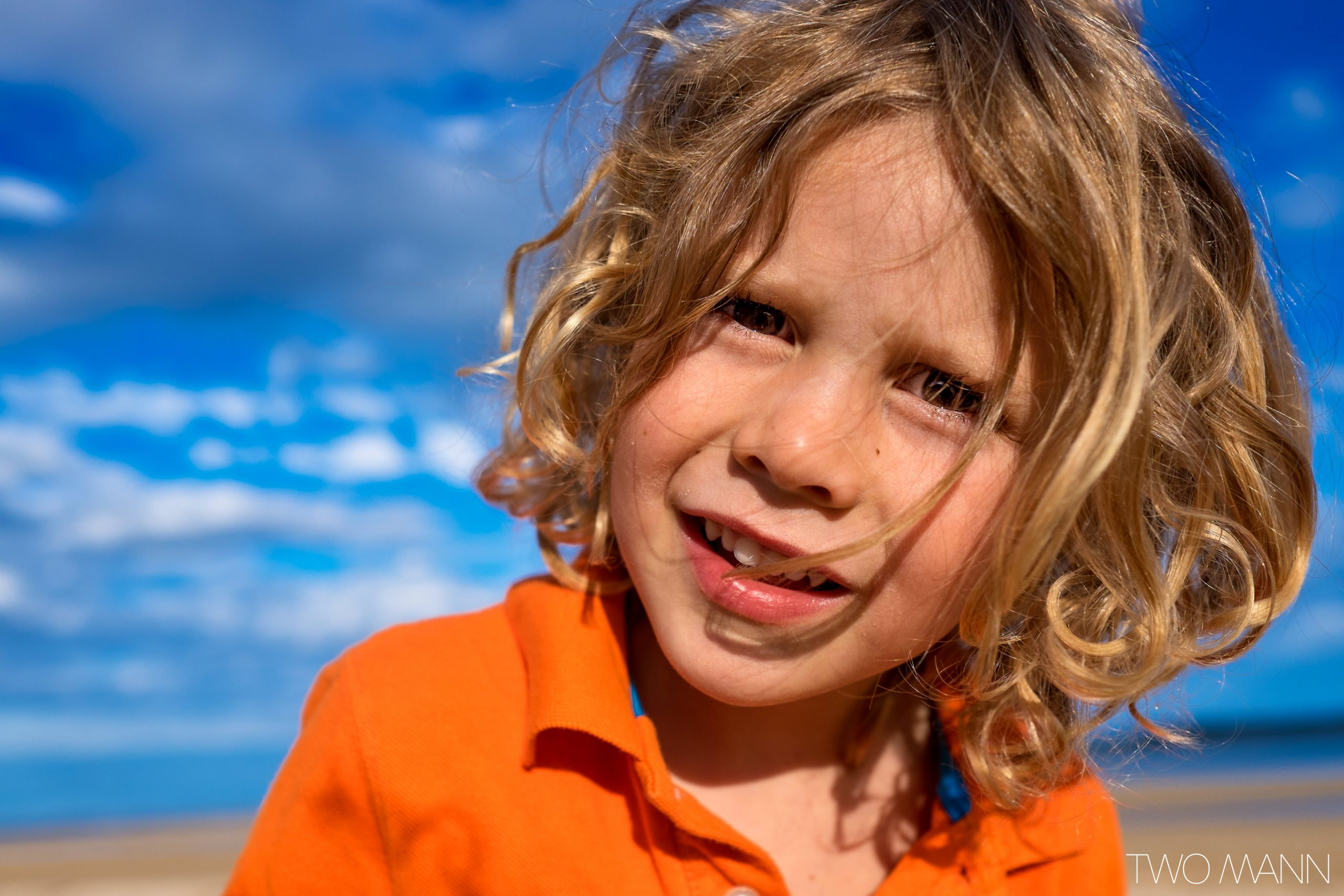 Close up of little boy with long blonde hair on the beach