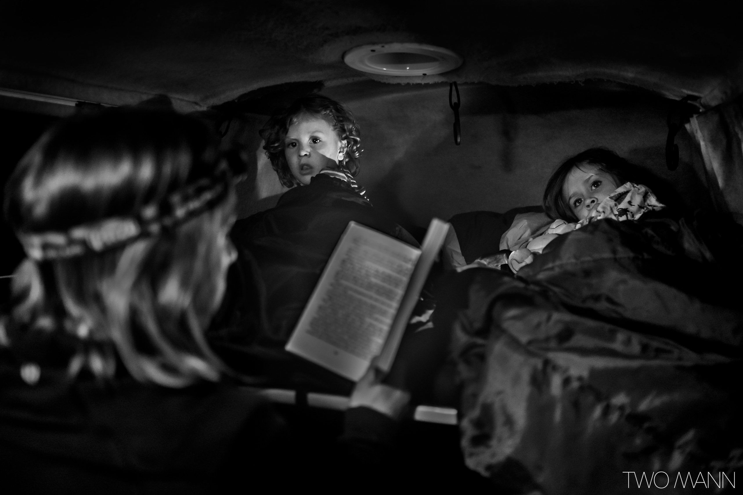 Two kids tucked in bed while mother reads them a bedtime story