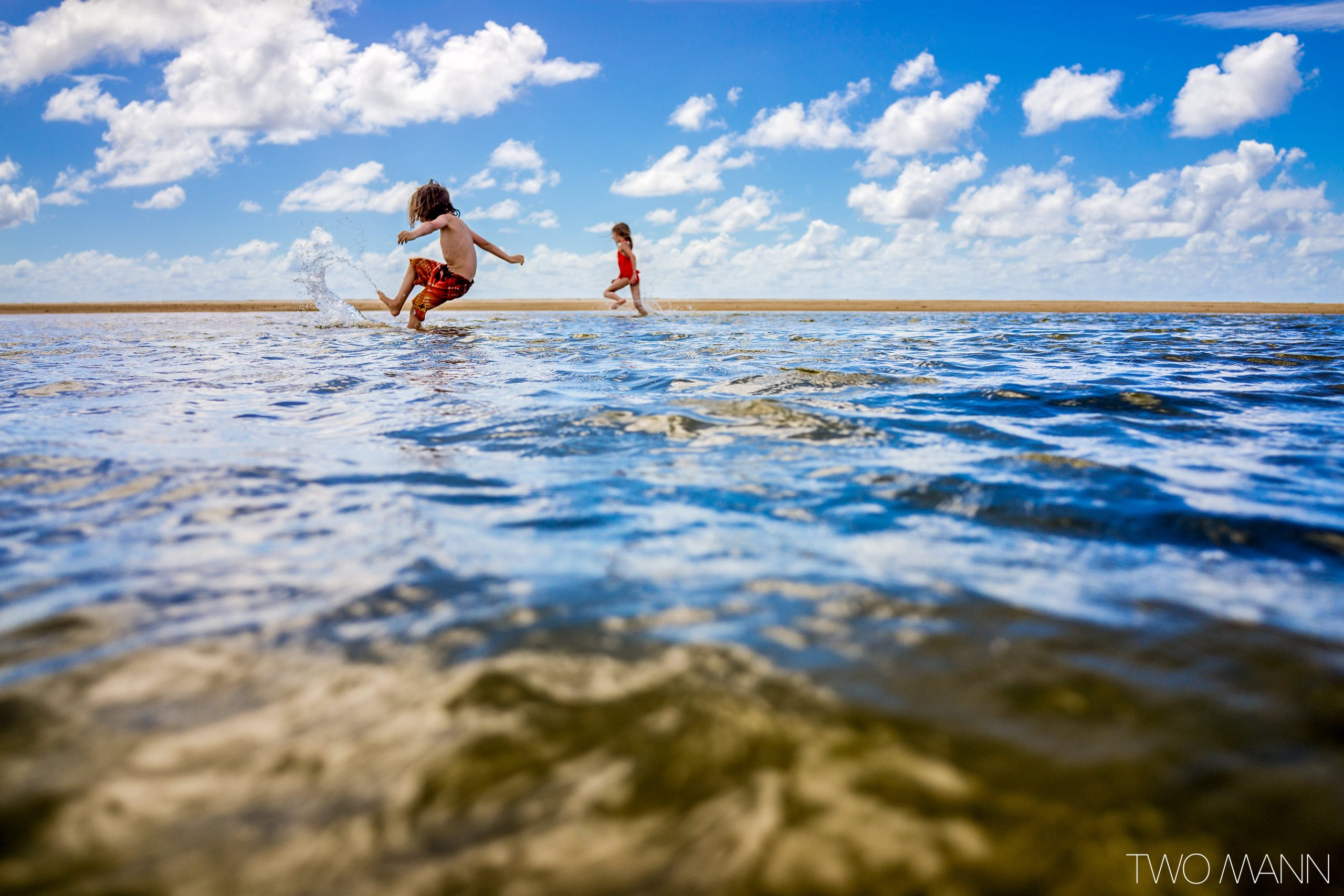 Little boy and girl kicking water at the beach