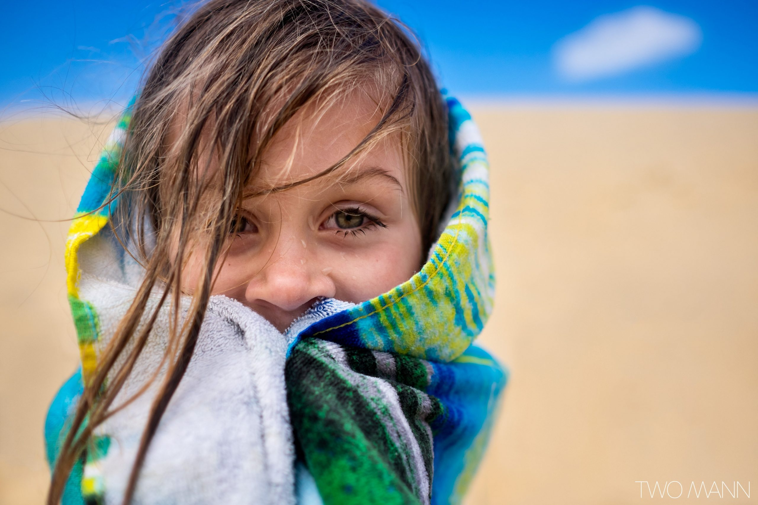 Young girl with towel wrapped around her face at the beach