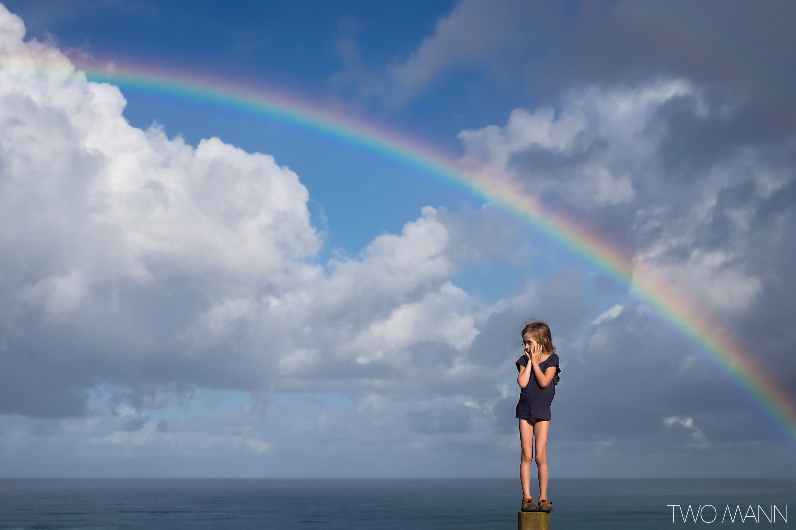 Young girl at the beach with rainbow in the sky
