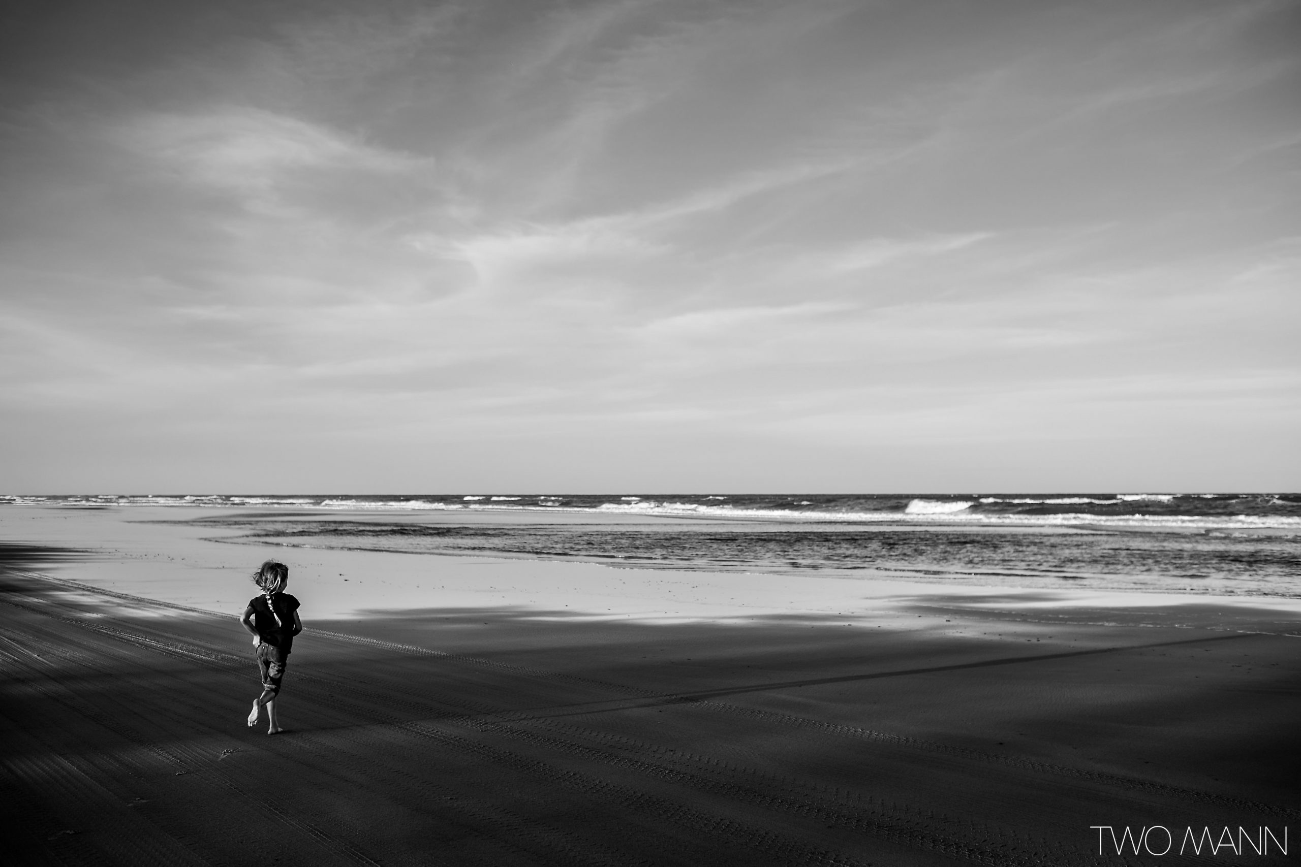 Young girl running towards ocean at the beach