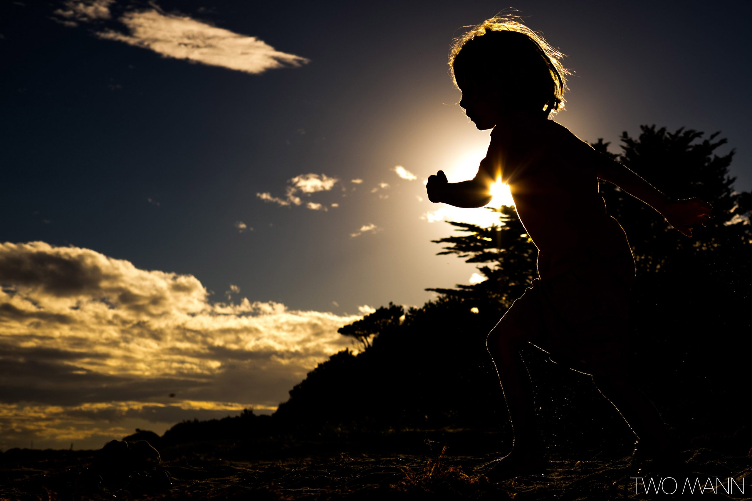 Silhouette of young boy running at sunset