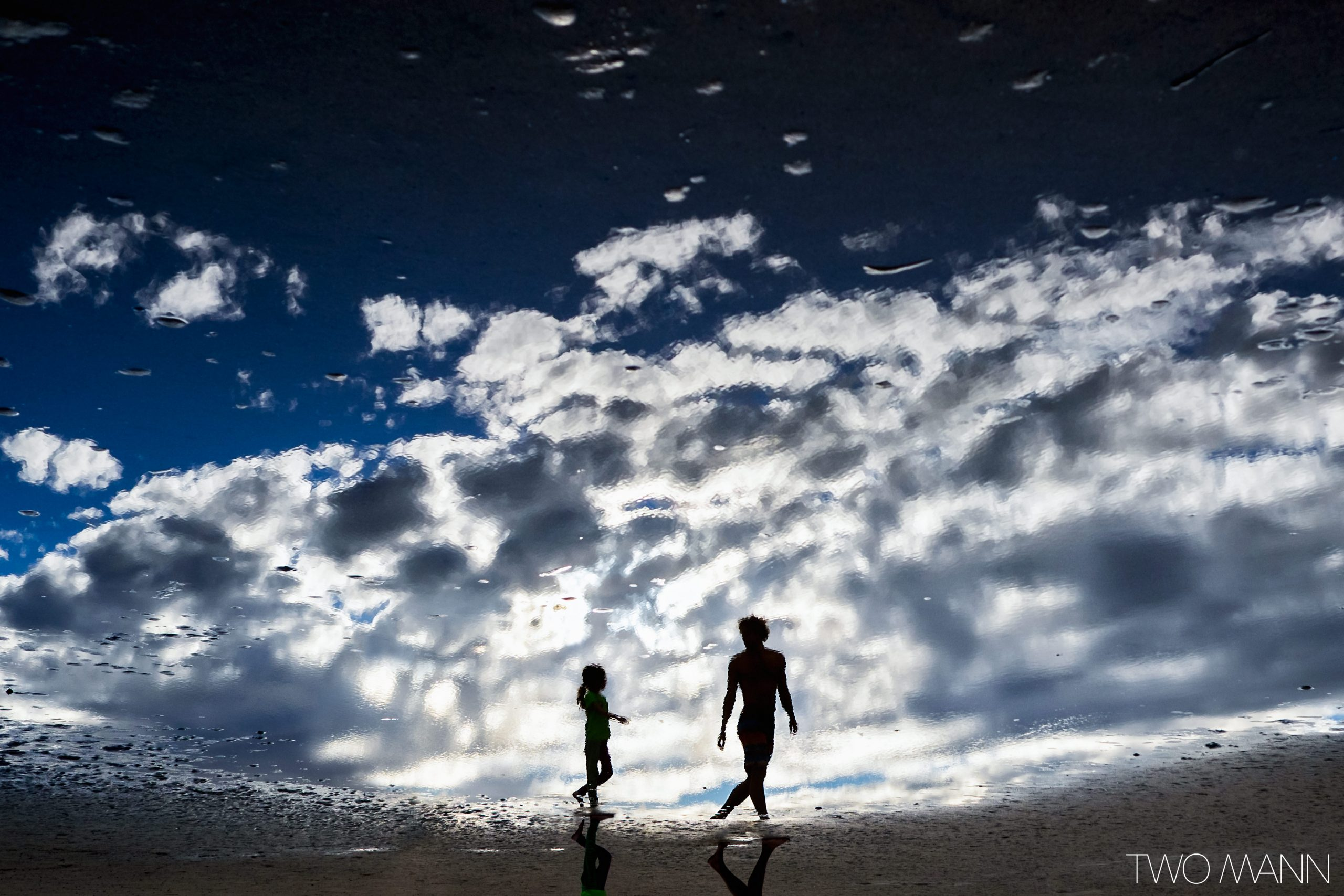 Silhouette of father and daughter walking on the beach