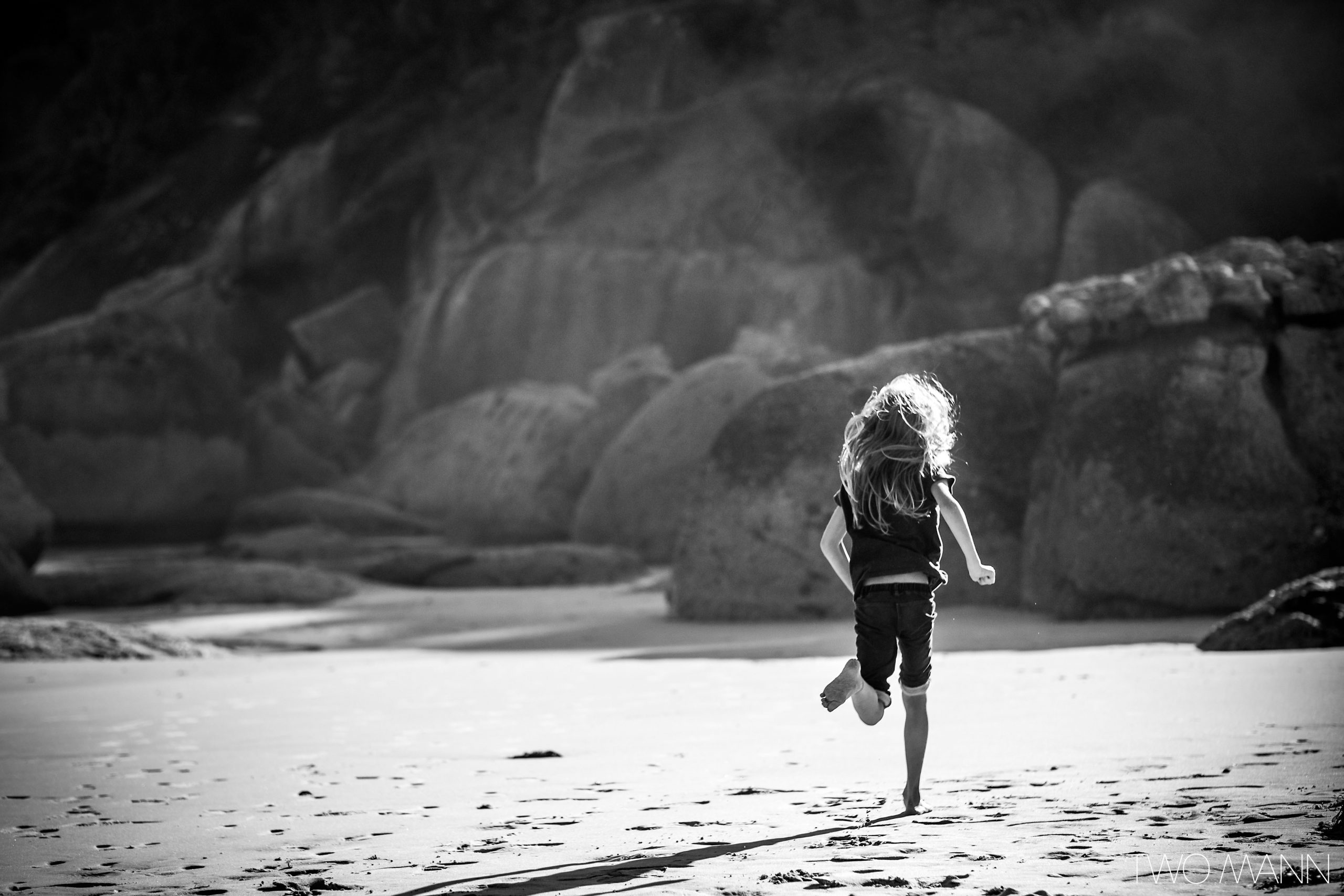 Young girl facing away from camera running on beach