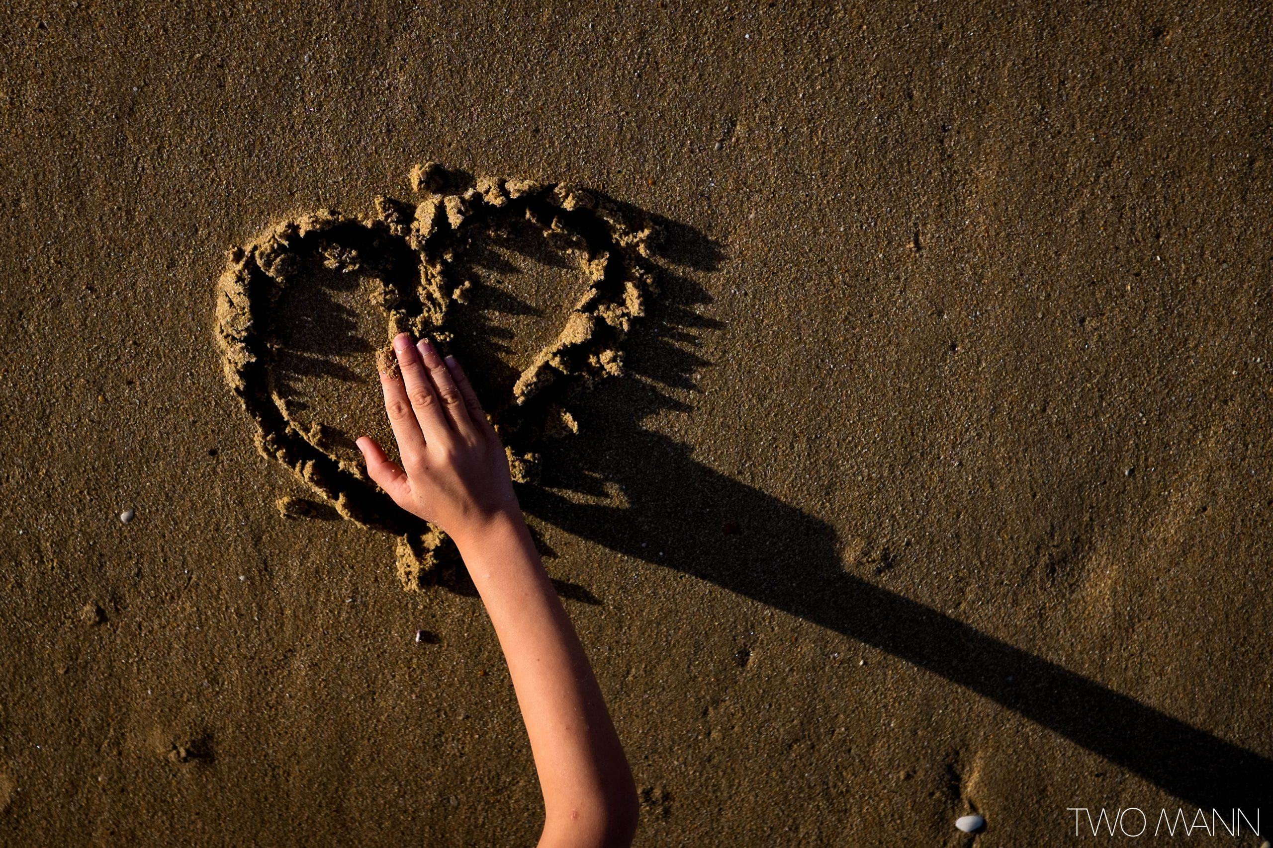 Young child draws a heart in the sand during sunset