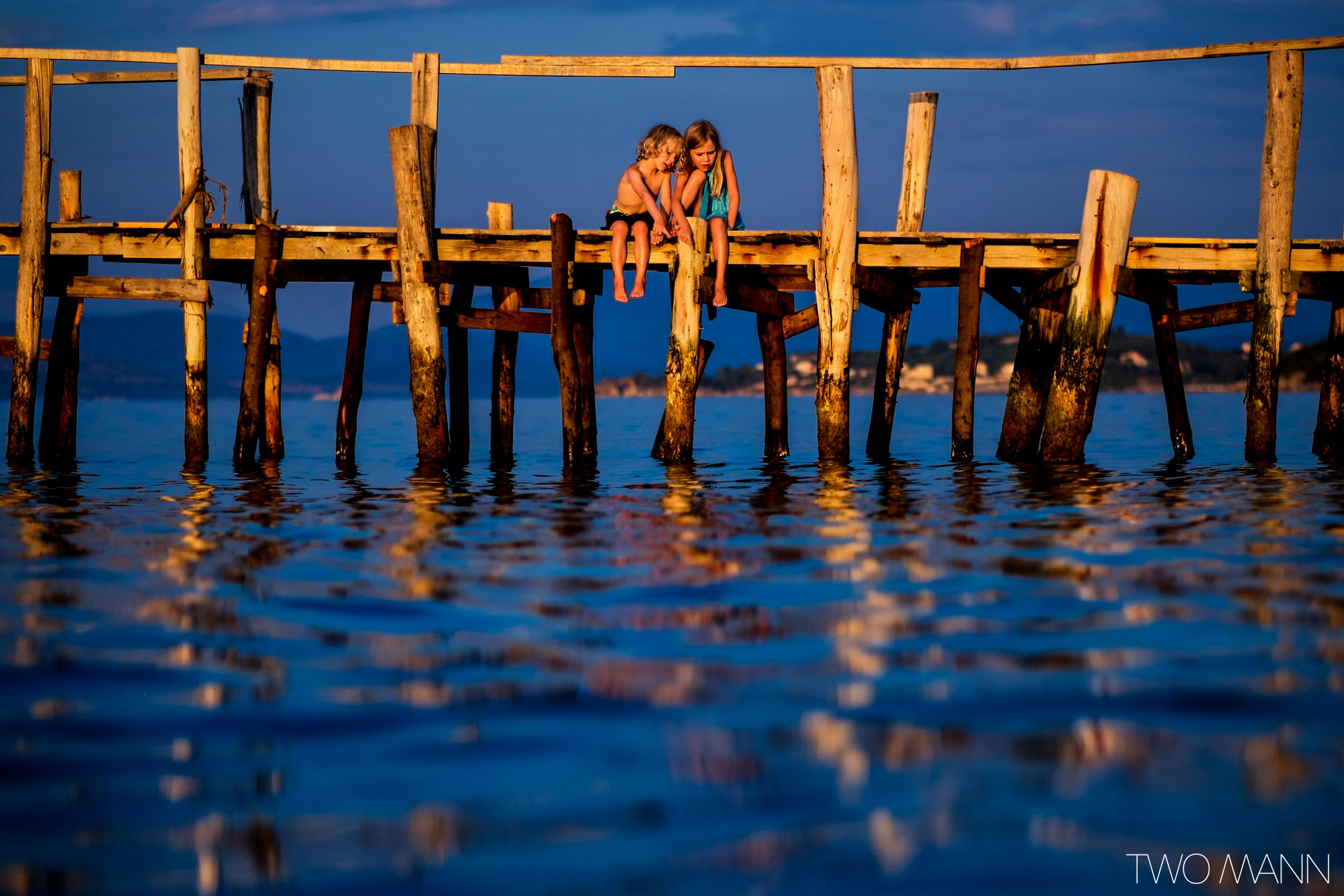 Young boy and girl sitting on pier pointing at water during sunset