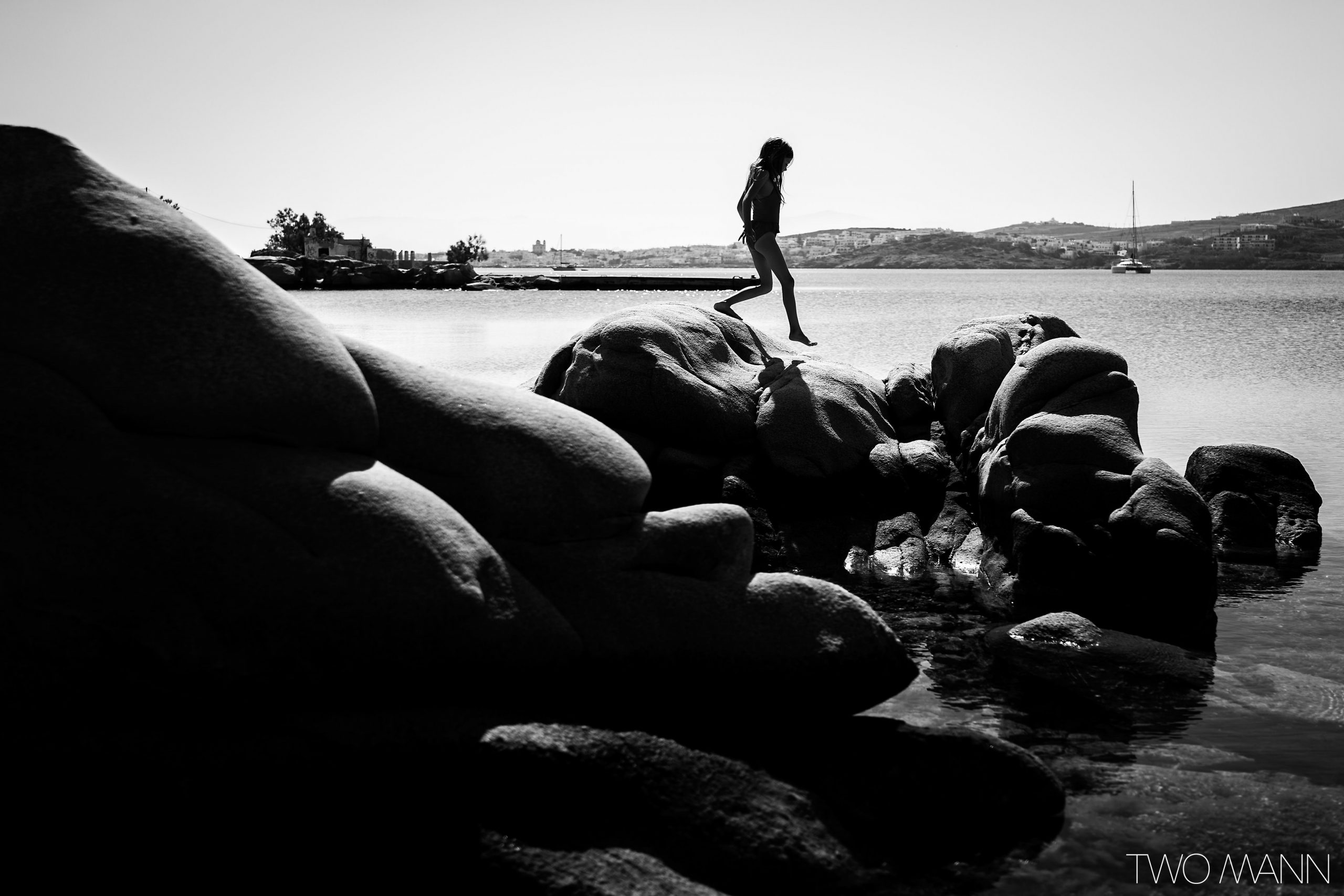 Young girl walking on large rocks on seashore
