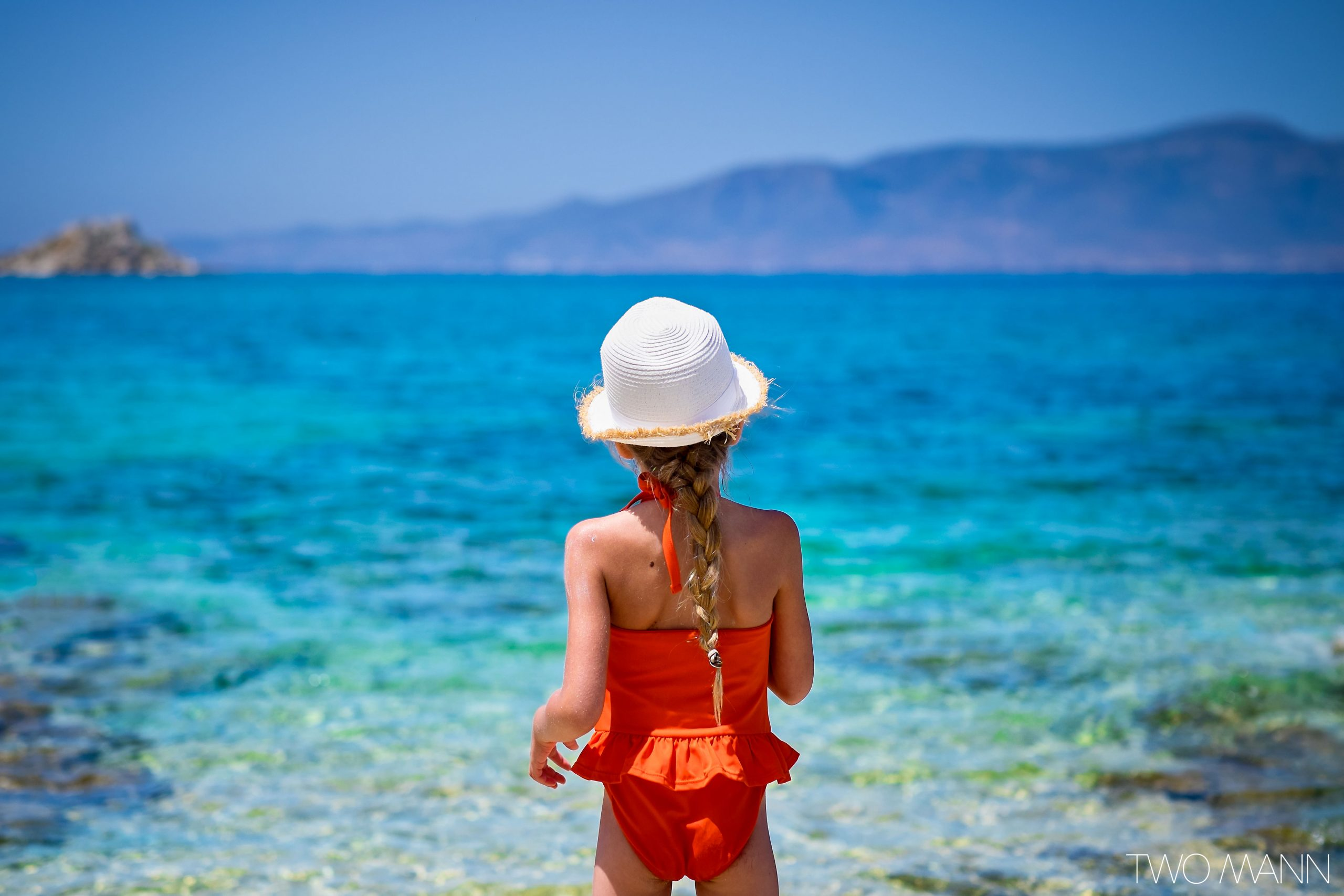 Young girl in orange swimsuit looking out into the sea