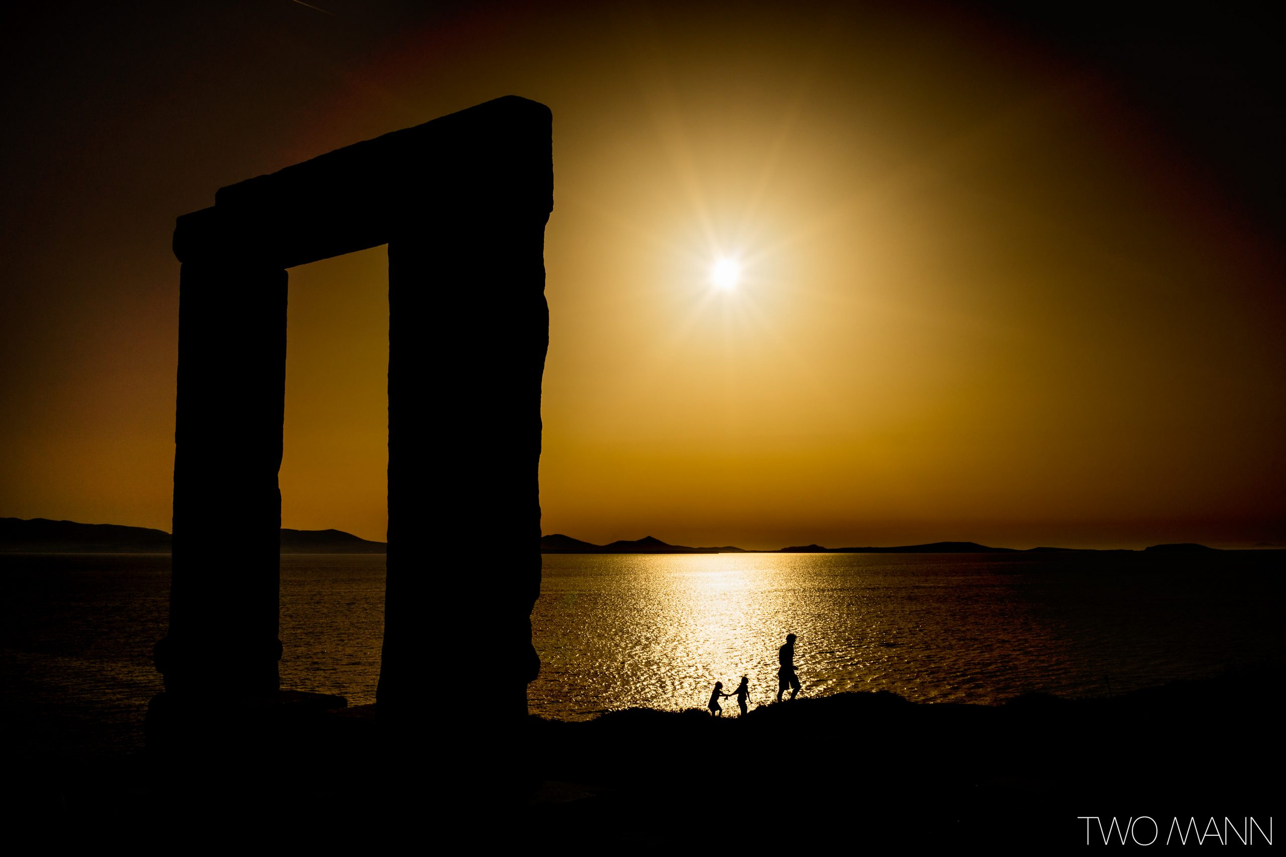 Father and kids walk along seashore beside Greek ruins at sunset