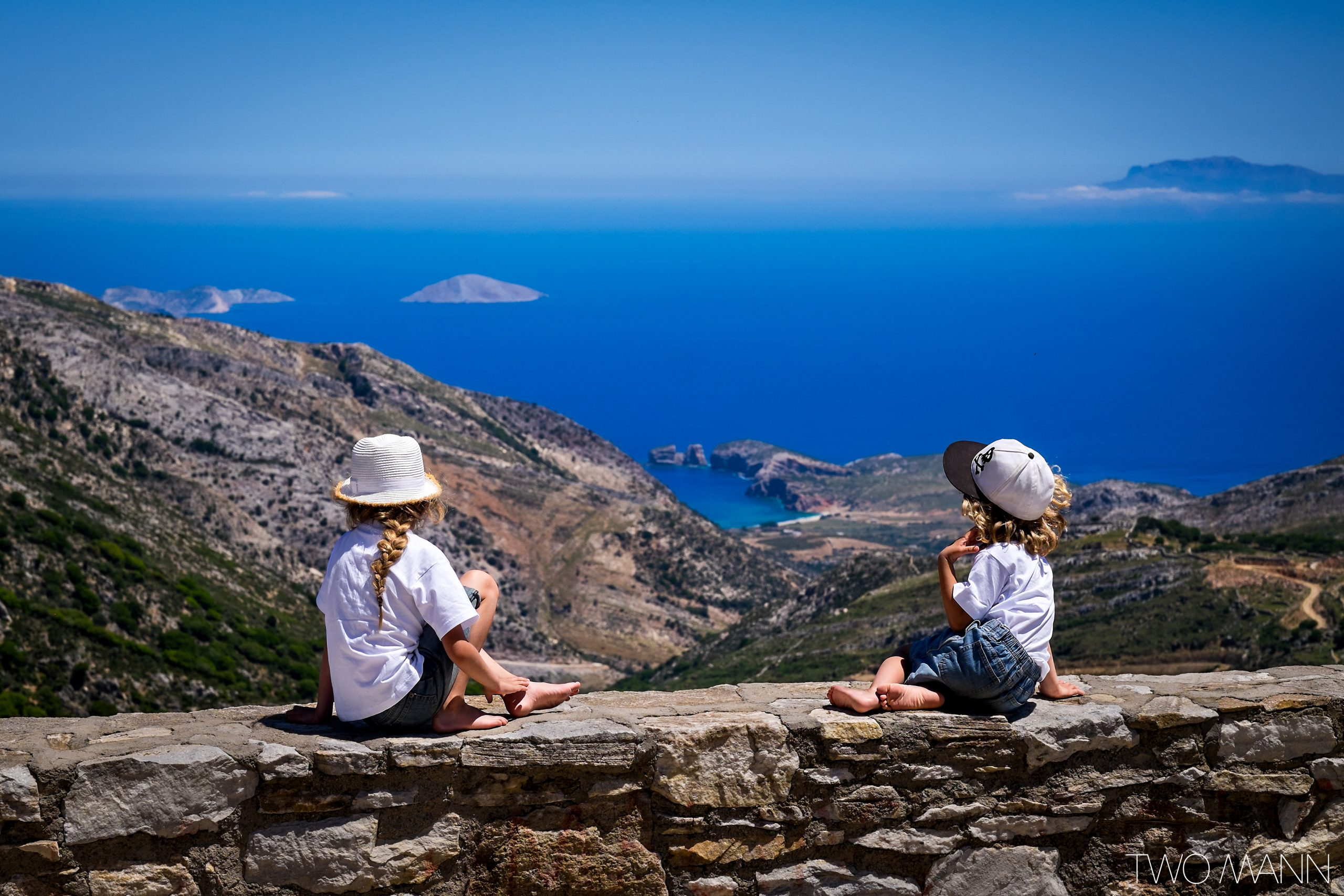 Two kids sitting on rock wall on hilltop staring out into sea