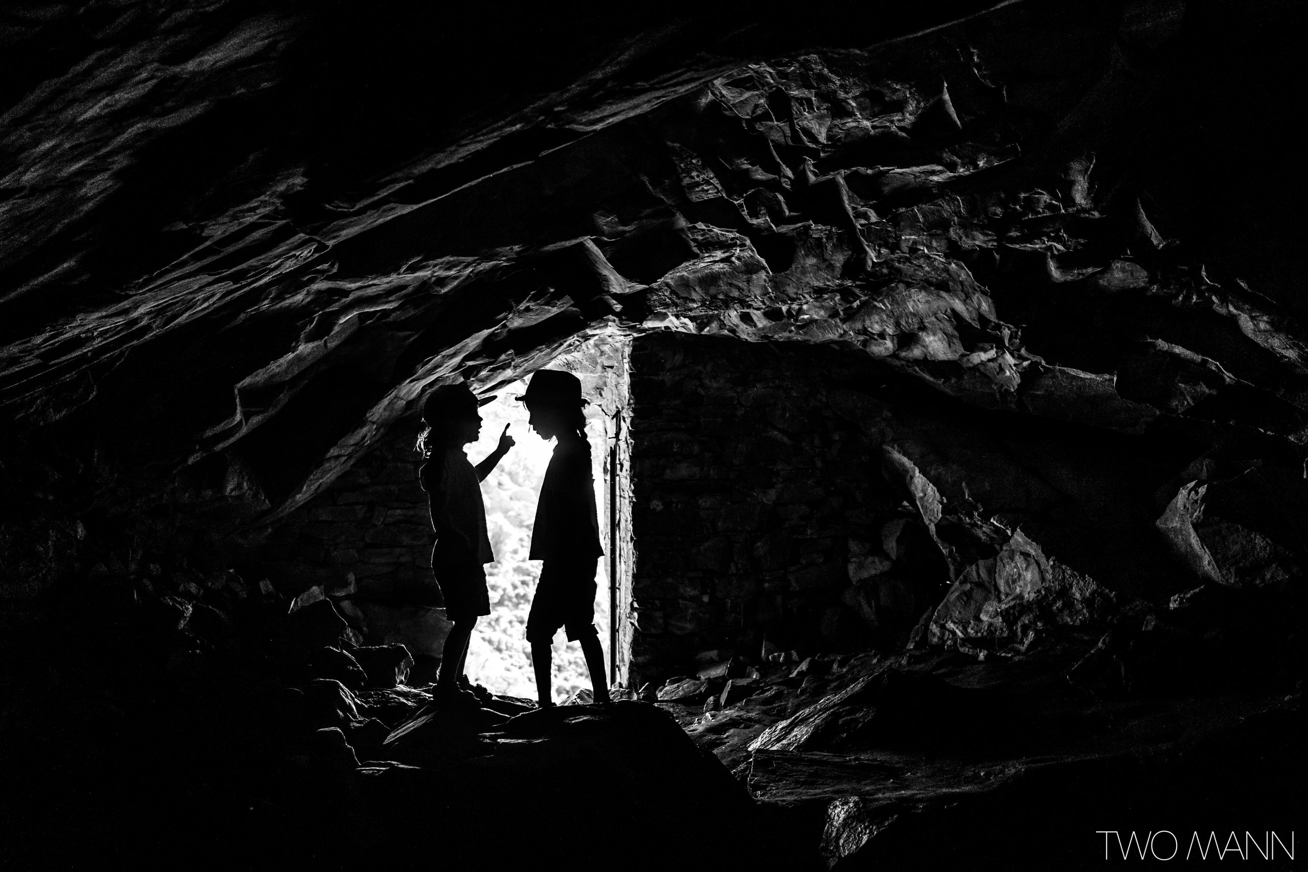Two kids in dark rocky tunnel stand face to face