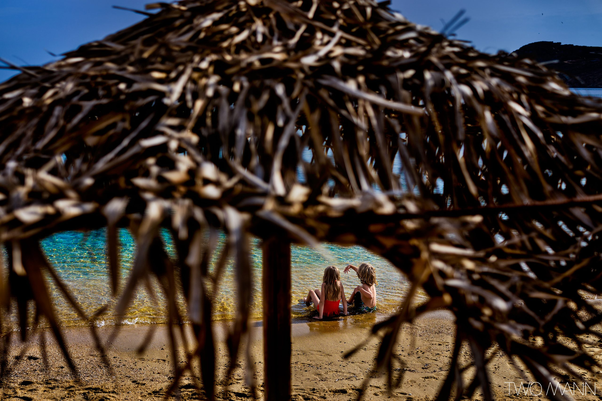 Two kids sitting on beach with straw hut behind them
