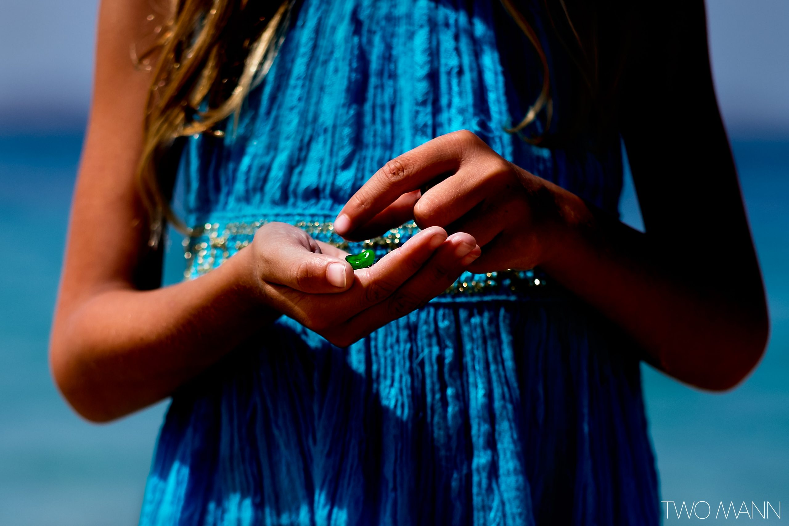 Young girl in blue dress playing with green bug in her hand