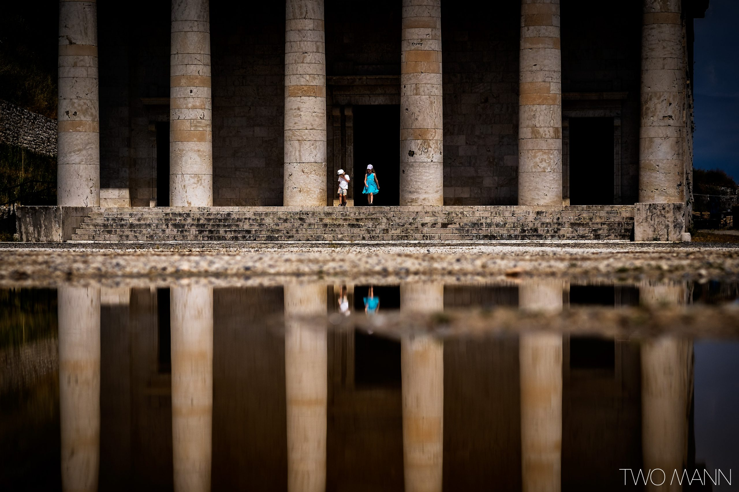 Two kids standing between giant pillars of Temple of Hephasestus