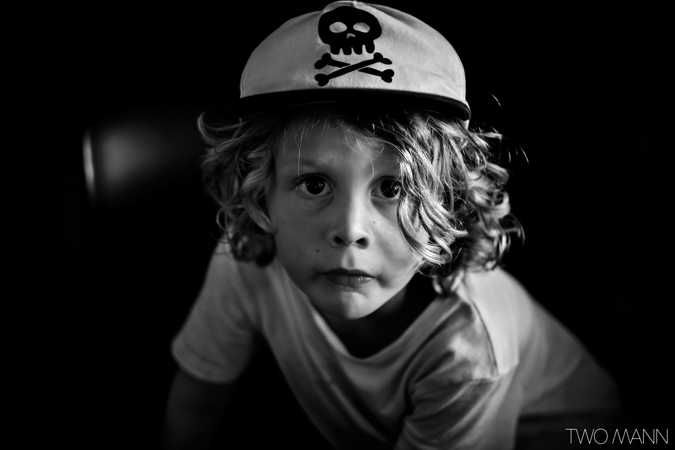 Young boy with curly blonde hair with skull and crossbones hat