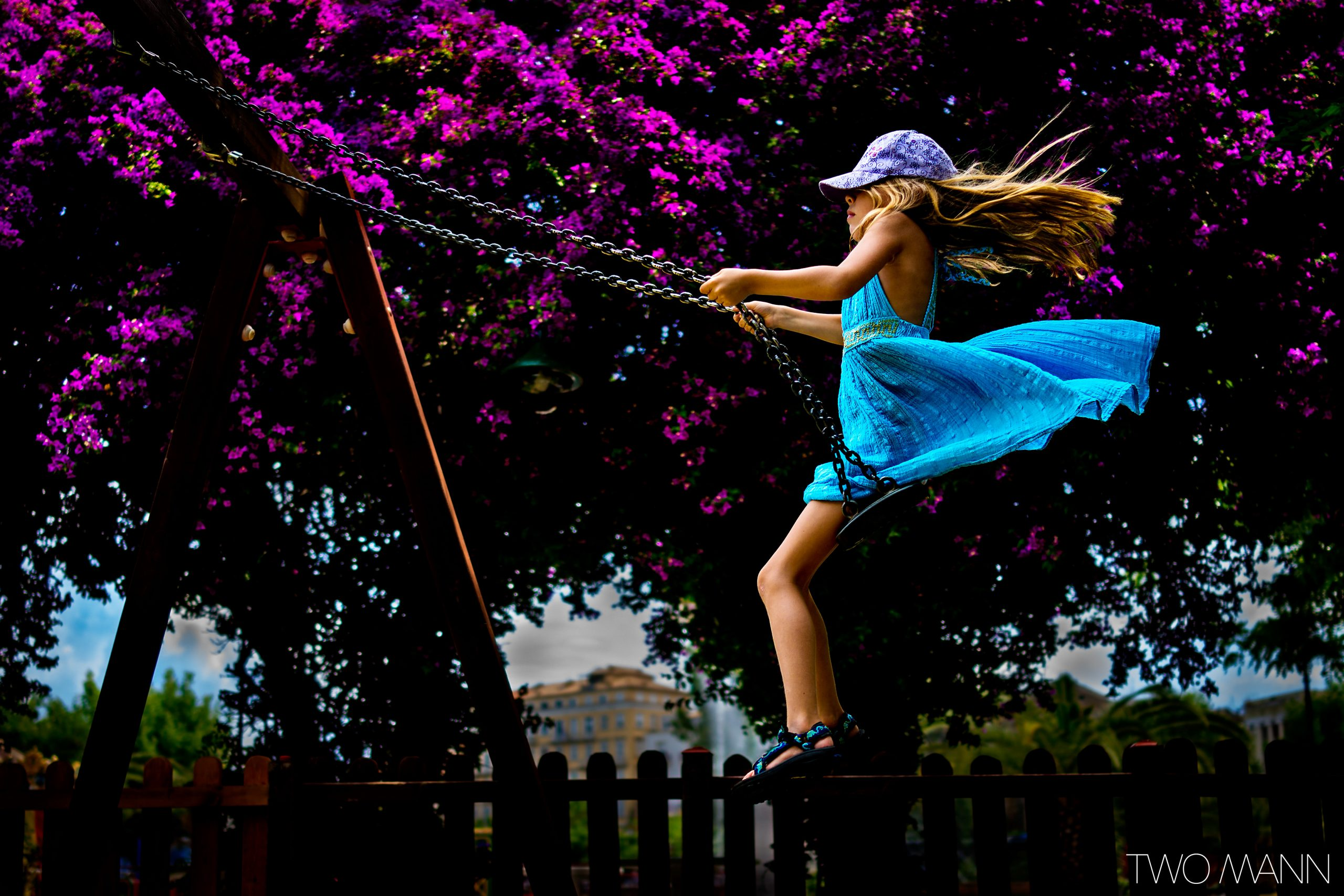 Girl swinging on swing in front of giant tree with violet flowers
