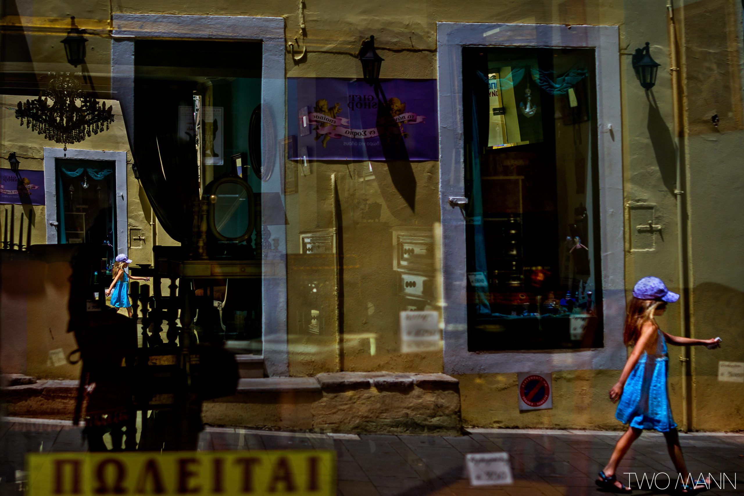 Reflection of young girl walking down street on store window