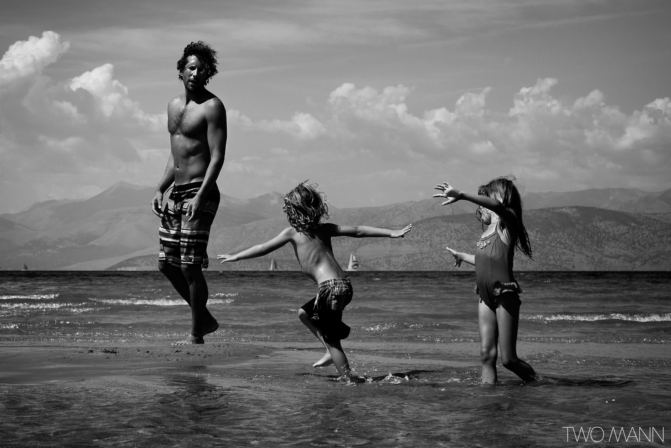 Father and kids walk along beach in shallow water