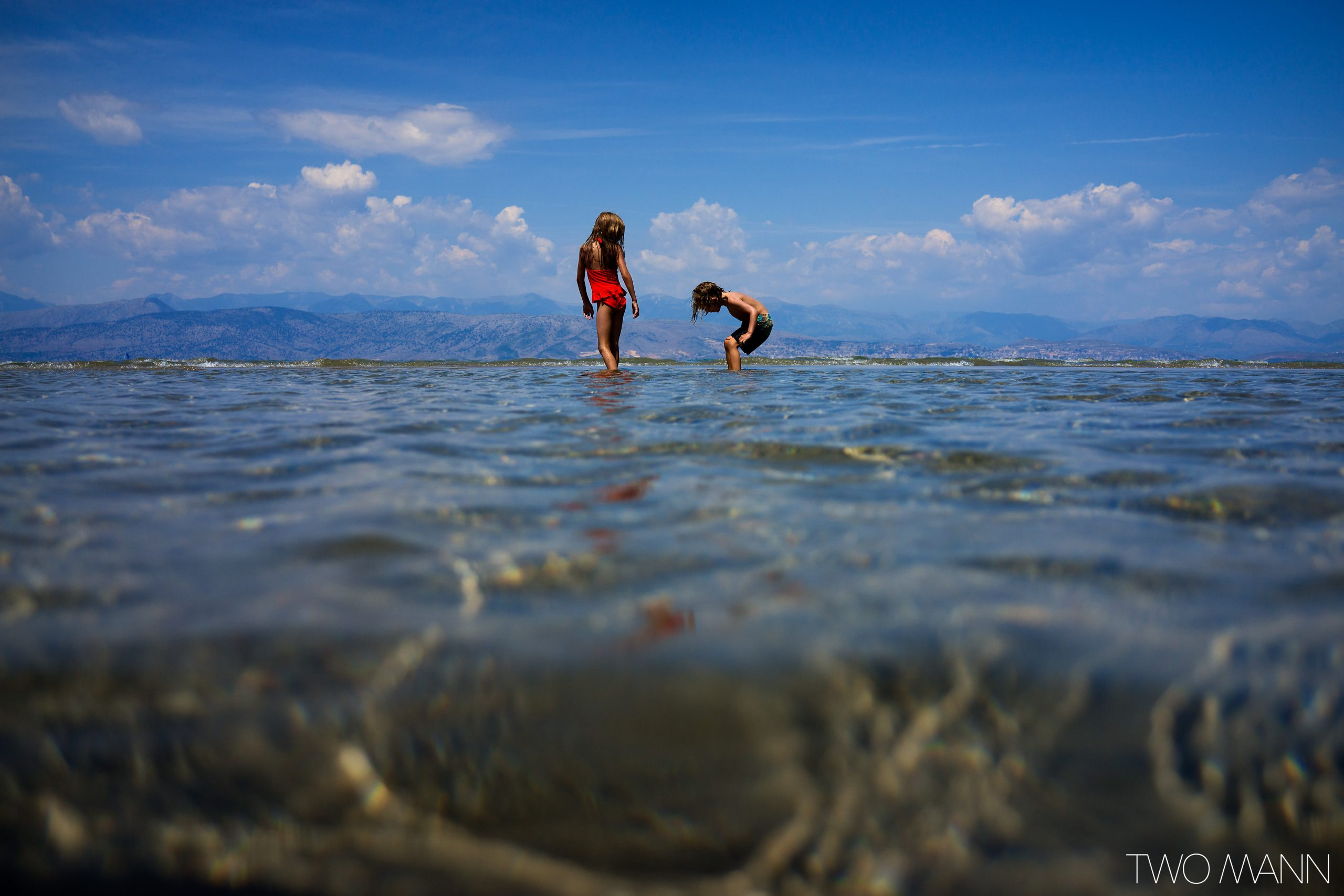 Boy and girl playing in shallow water on the beach