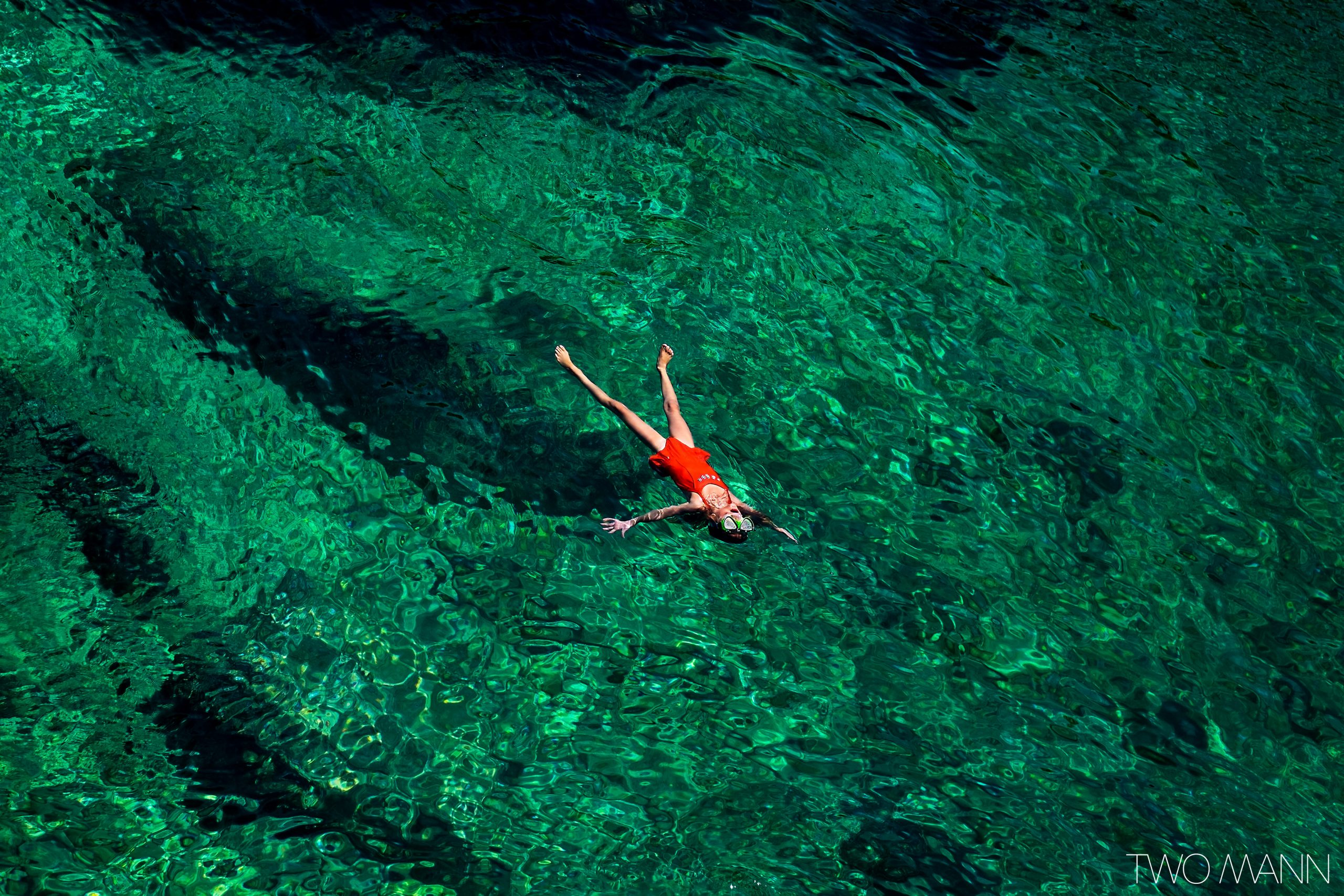 Girl floating in emerald green sea water