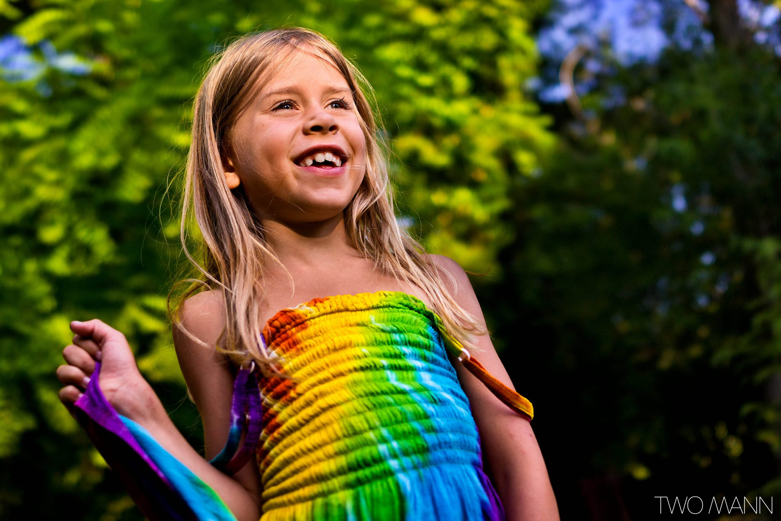 Young girl in tie dye dress smiling