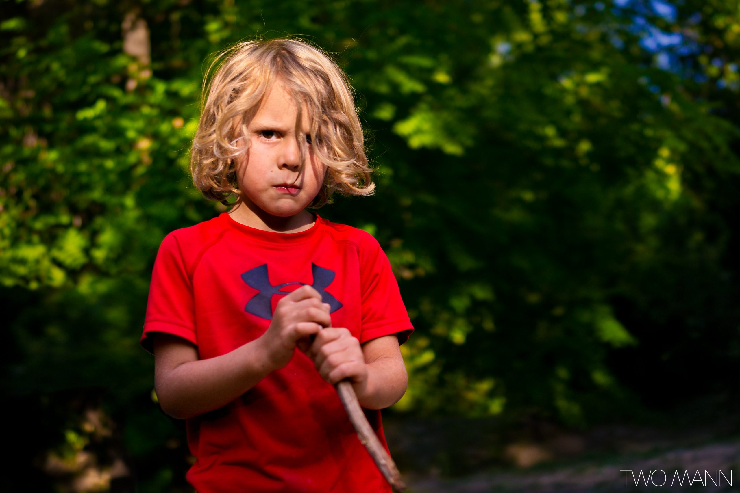 Young boy with long blonde hair with disappointed face