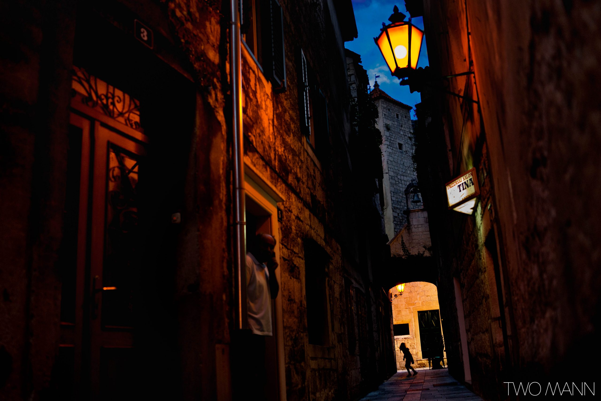 Young girl playing on narrow city street at dusk