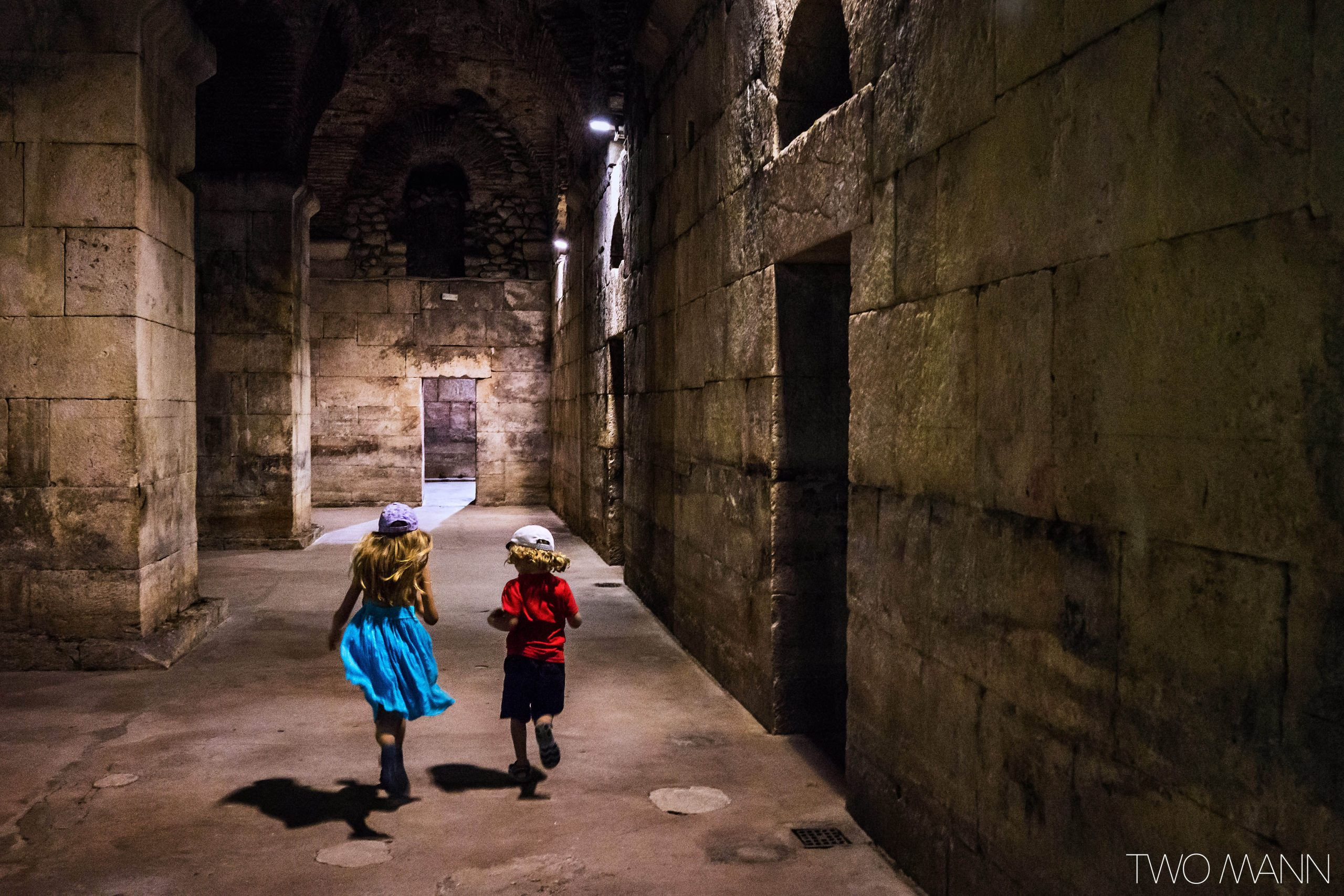 Young girl and boy run down stone hallway in old palace