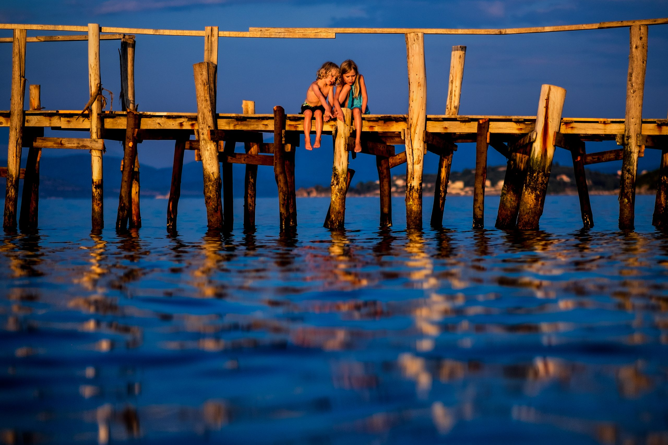 Two children relax on pier at sunset