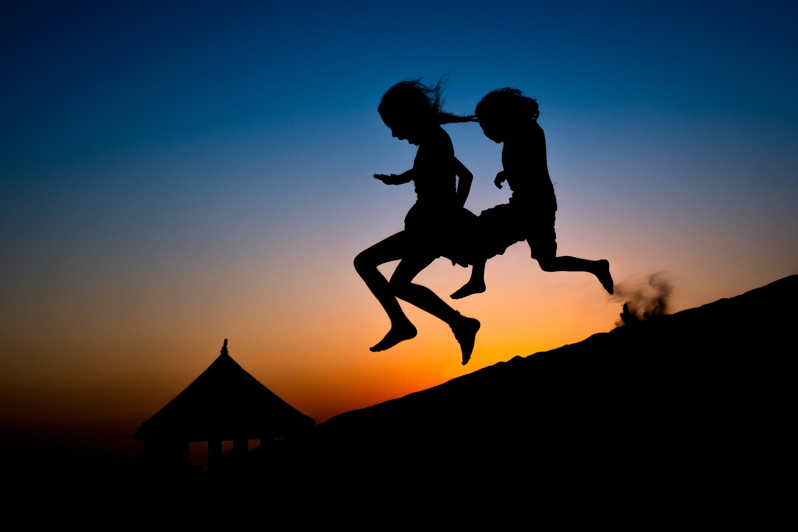 Two children run down hill at dusk