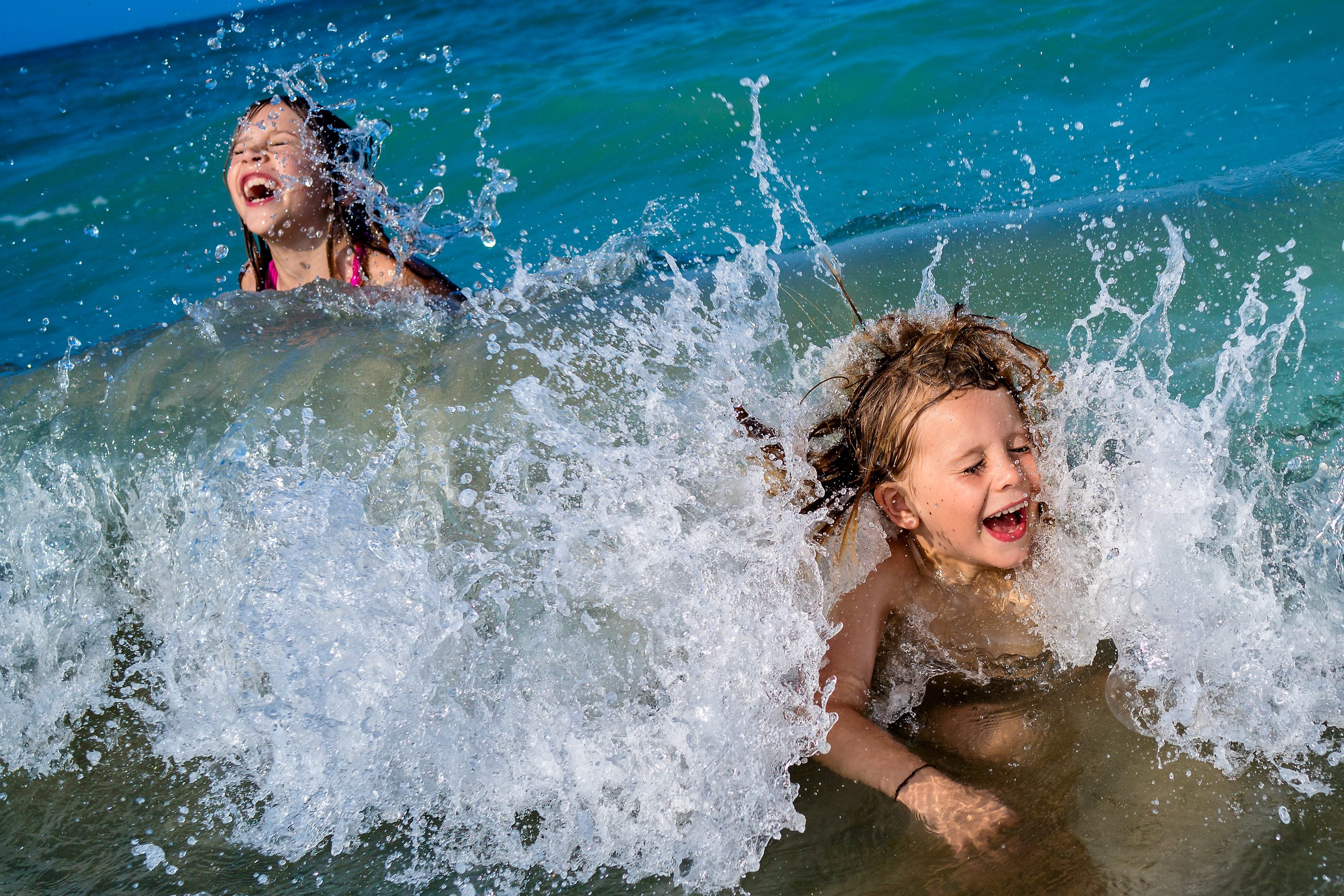 Two children laugh while getting splashed by waves on beach