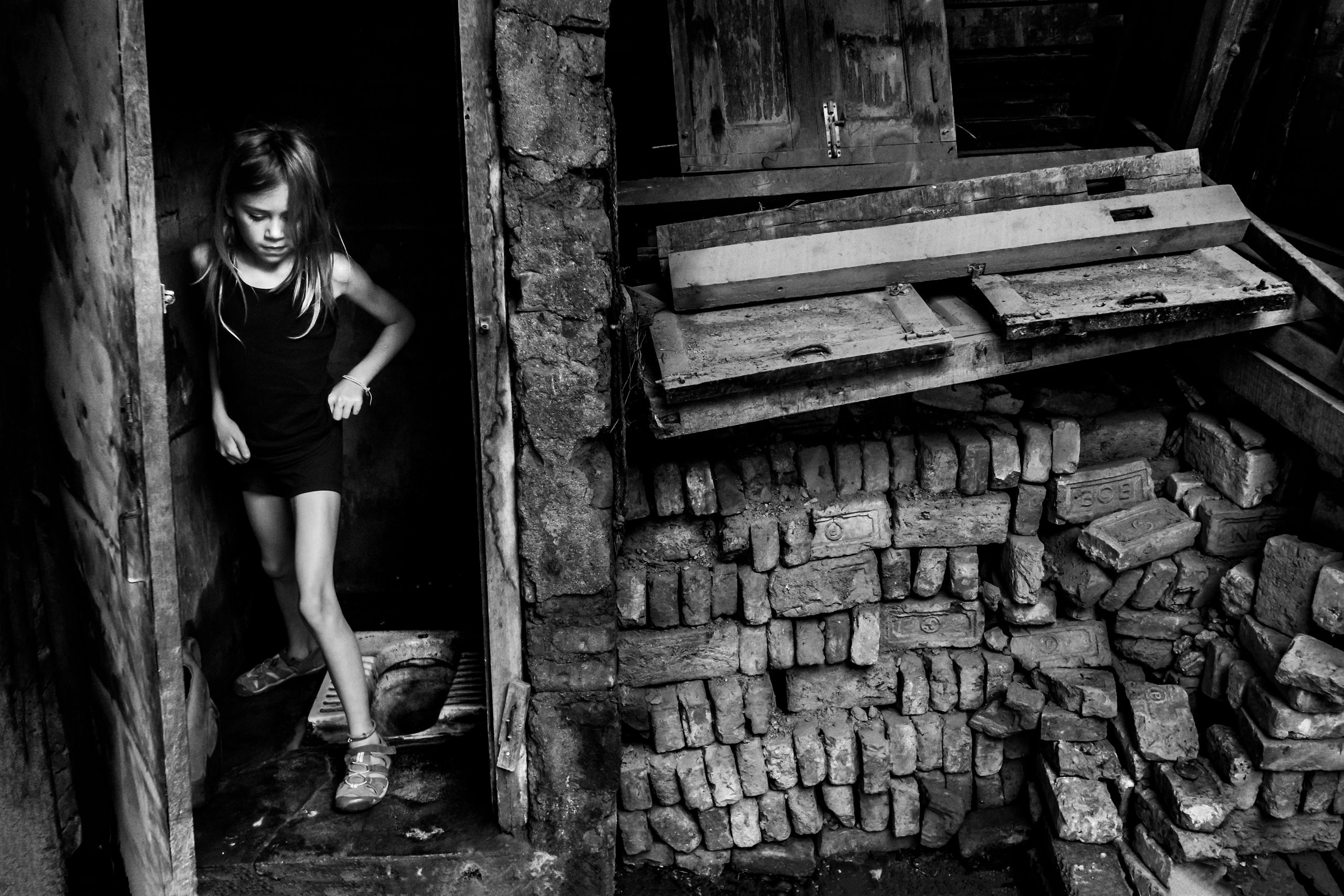 Young girl standing in front of Nepalese house