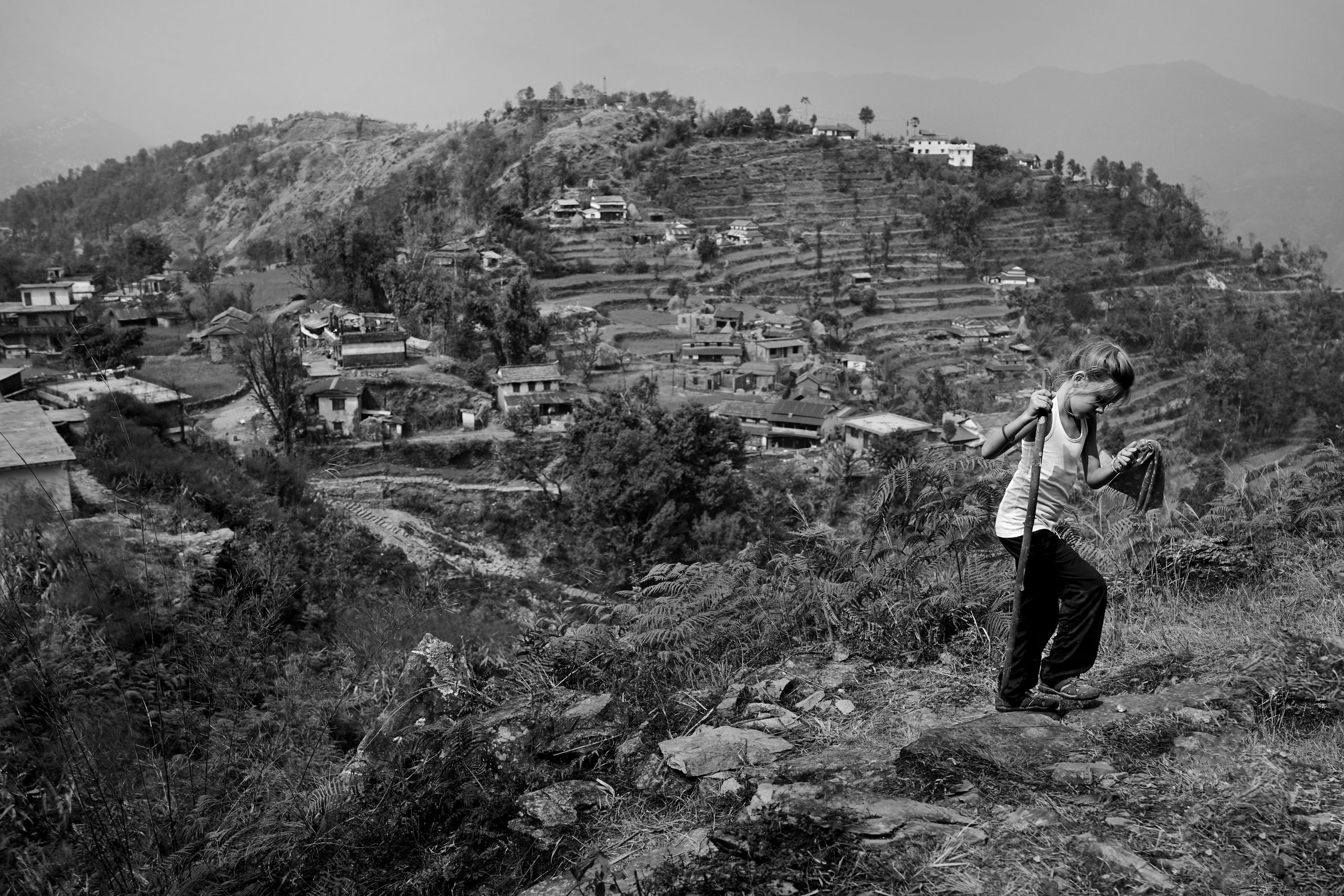 Young girl hiking in Nepal with village below