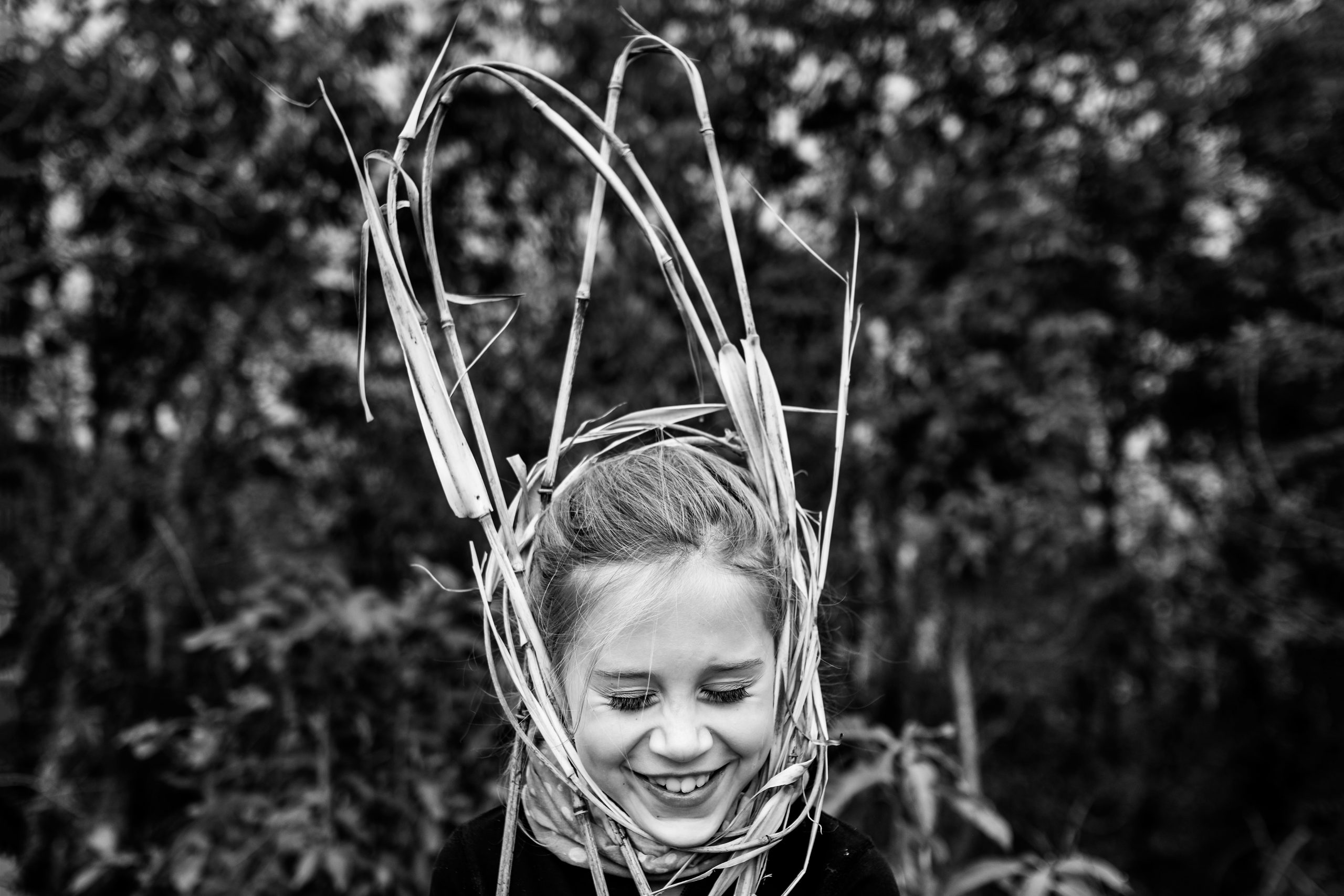 Young girl wrapped up in thick straw laughing