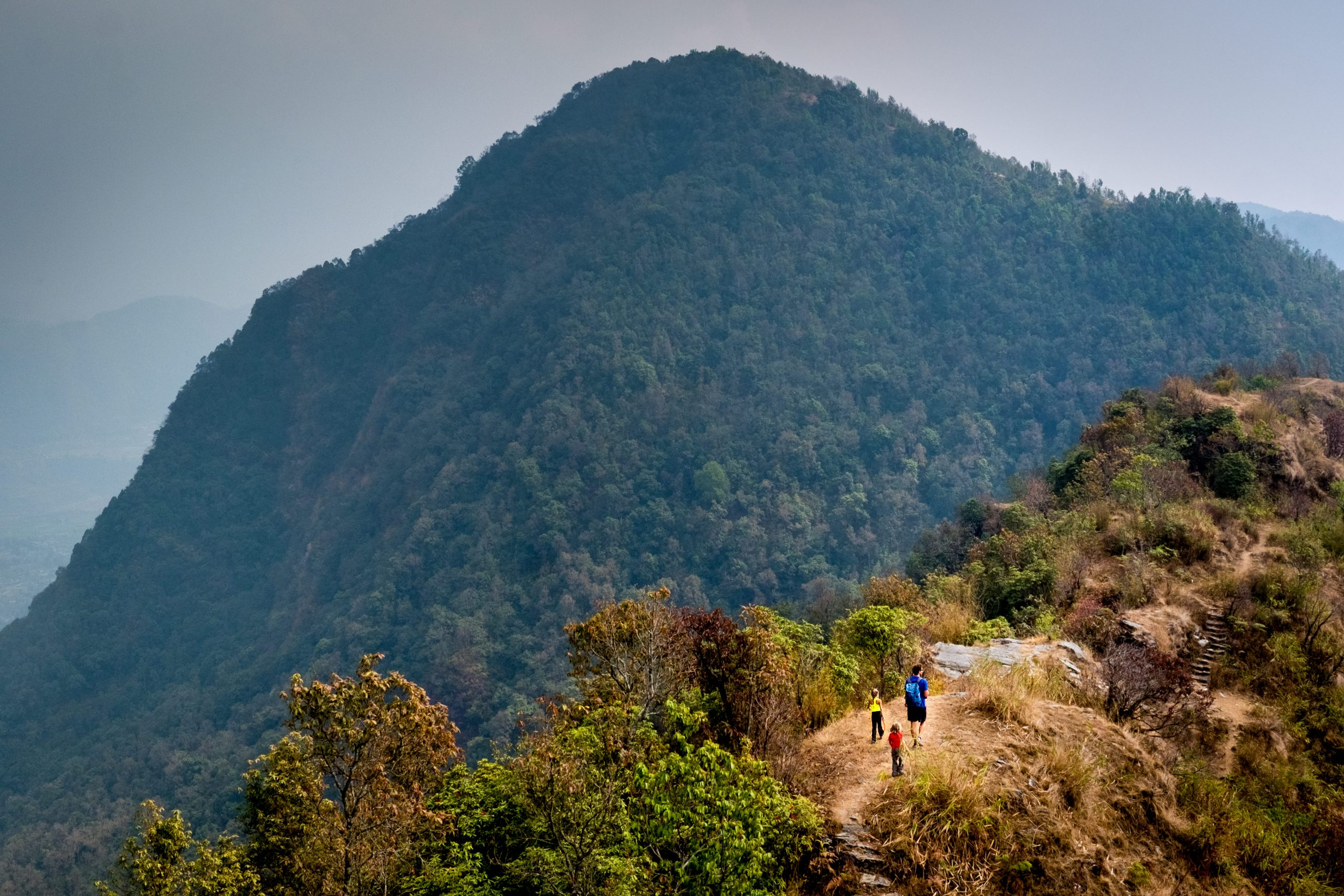 Father and kids hiking up hill in Nepal