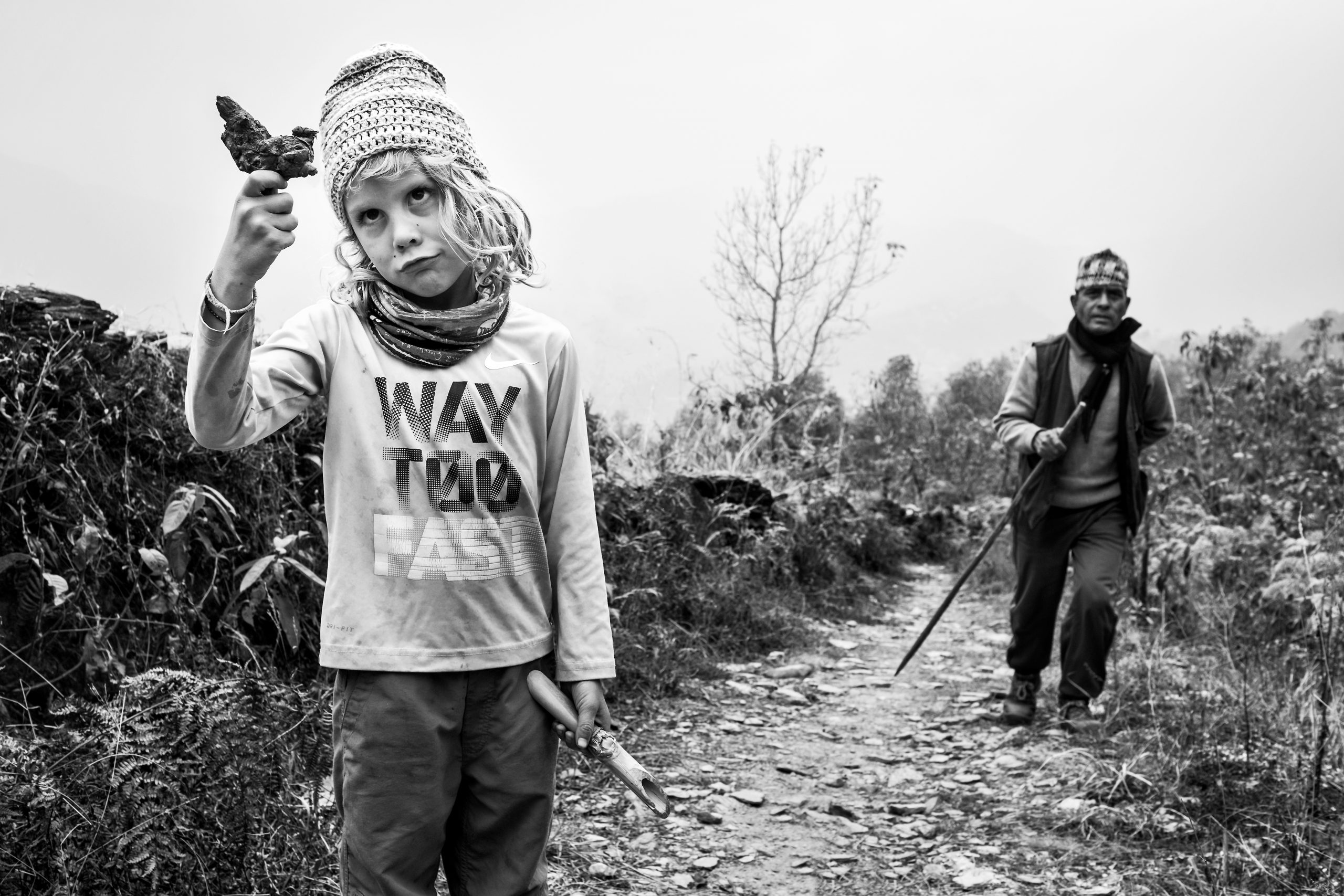 Young boy examining rock in front of local Nepalese farmer