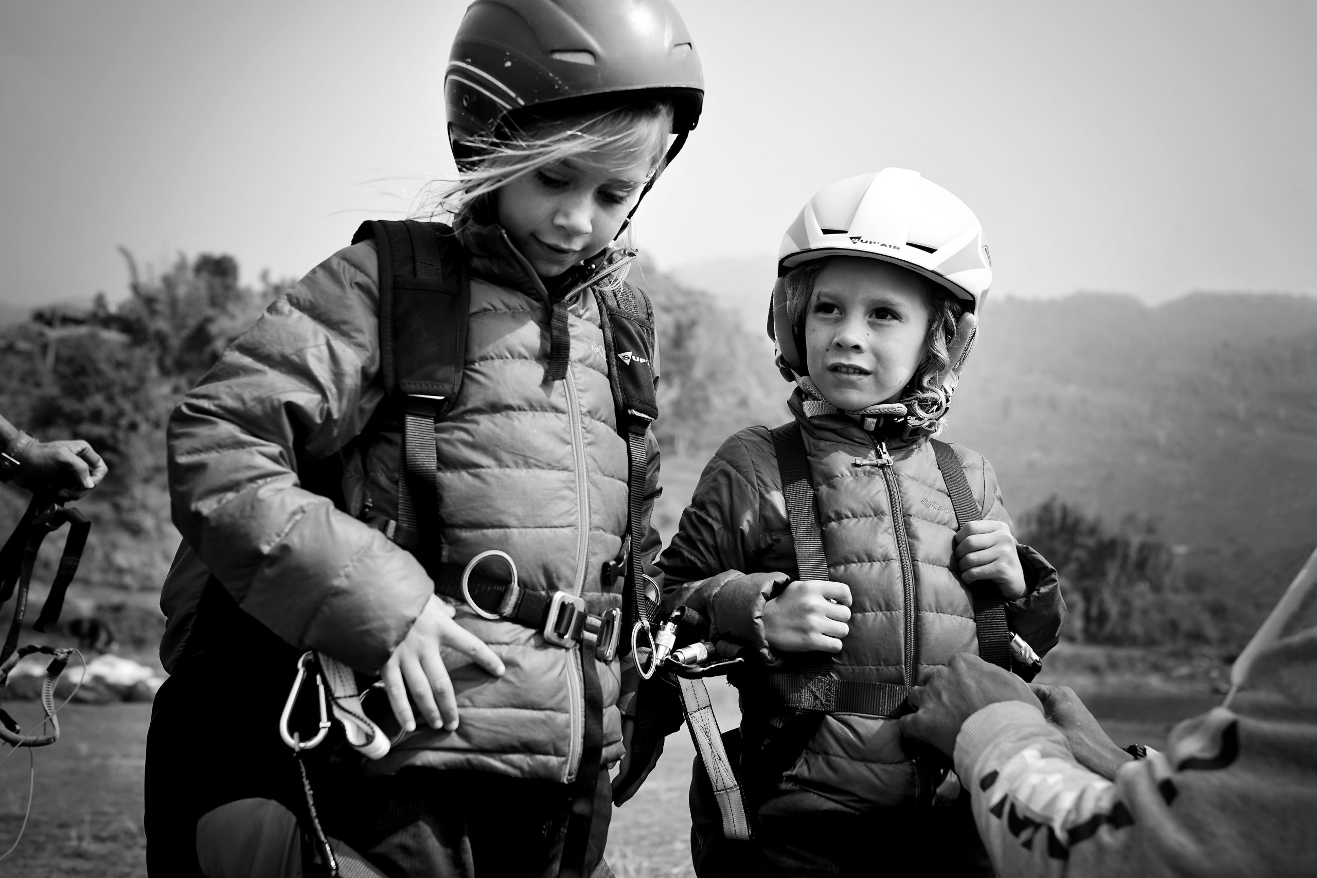 Young boy and girl tightening safety harnesses
