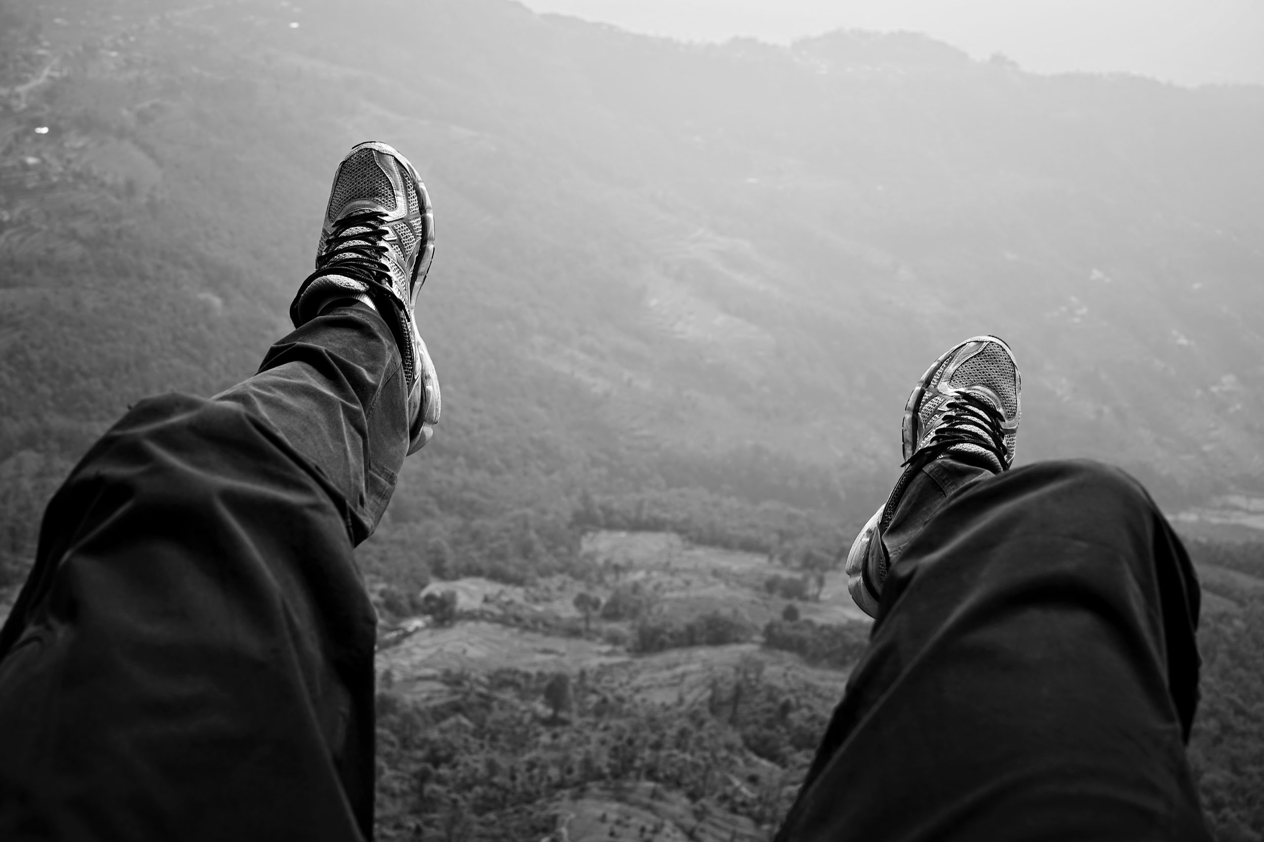 Man snaps picture while paragliding with feet dangling in air