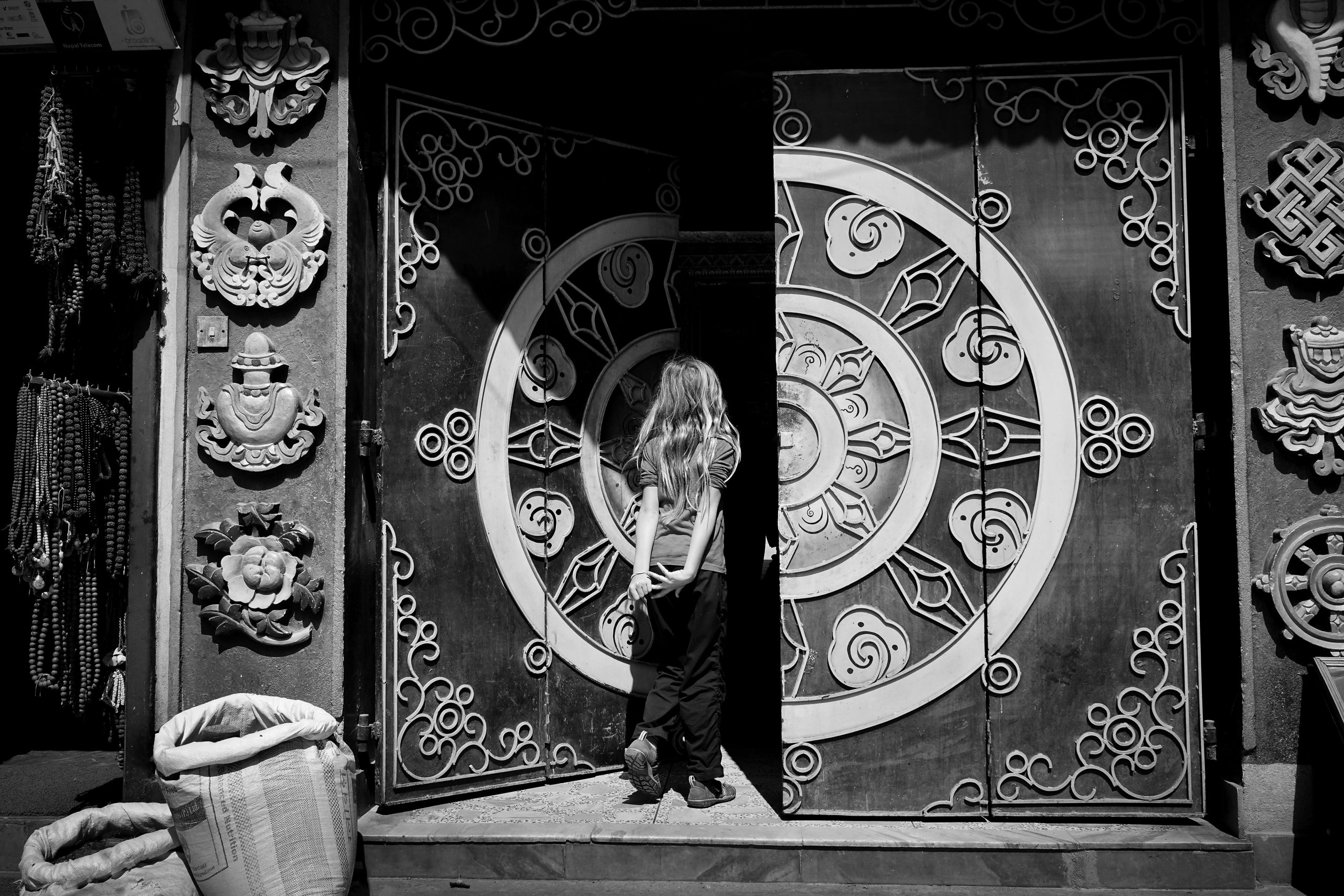 Young girl walking inside Nepalese temple with large wooden traditional doors