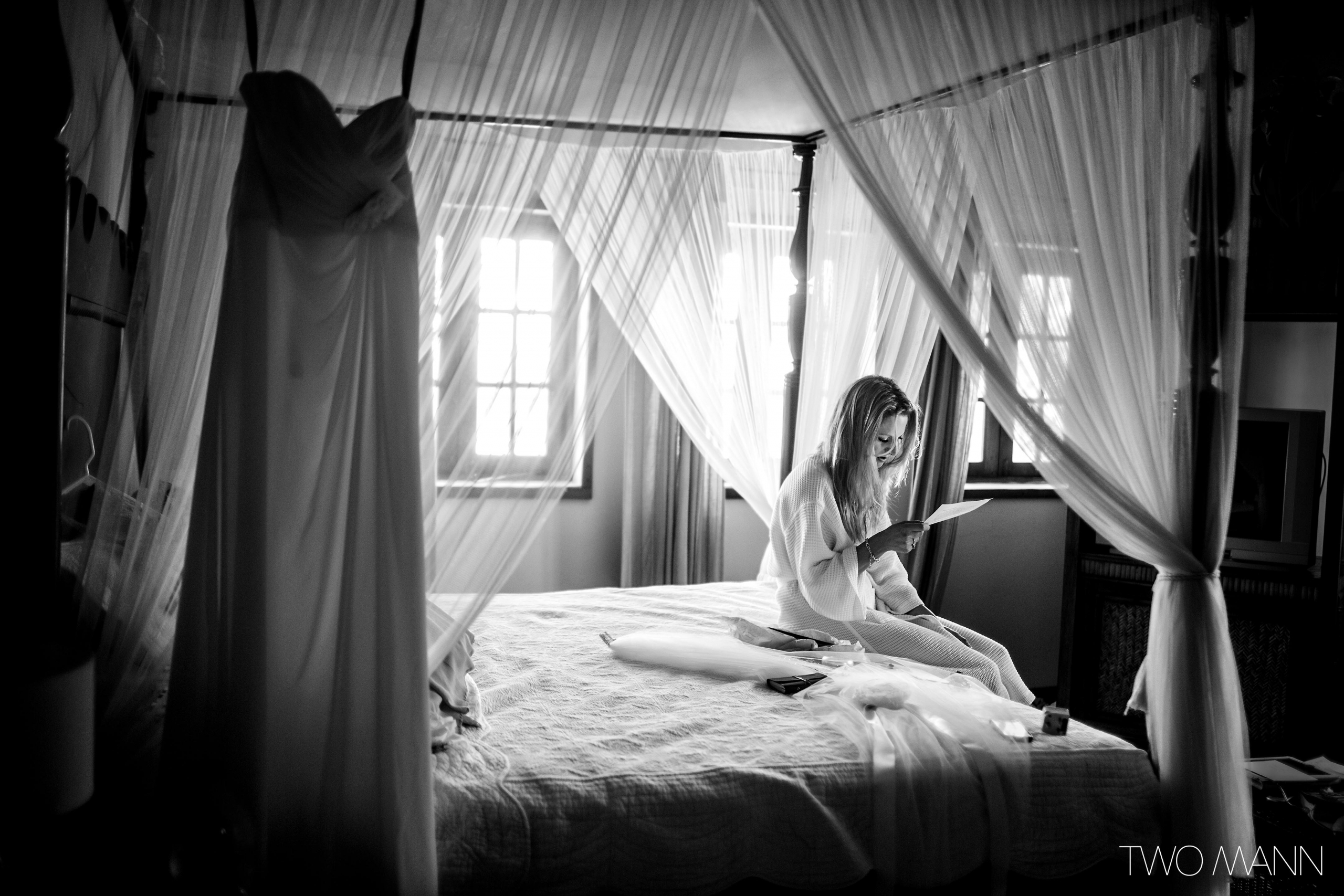 a bride sitting on bed reviewing her wedding speech