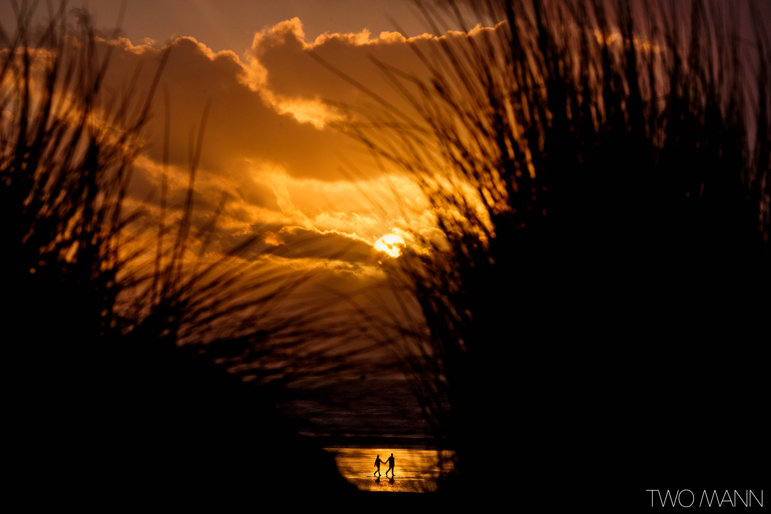bride and groom walking on the beach at sunset in Devonshire United Kingdom