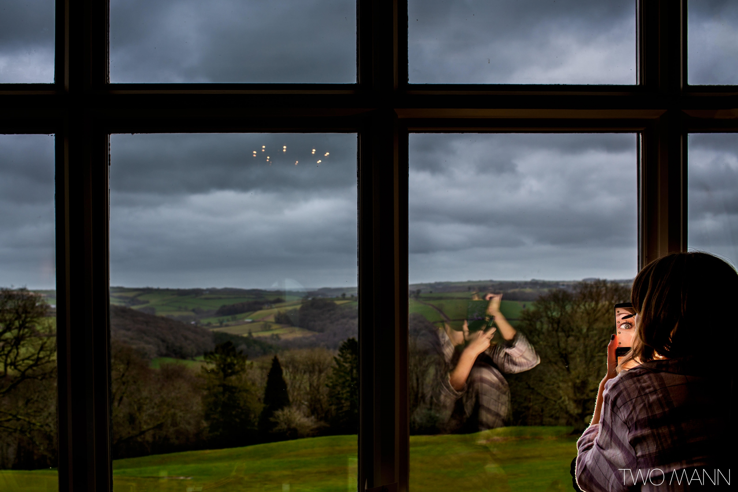 a bride doing her makeup in the room with fields seen through windows