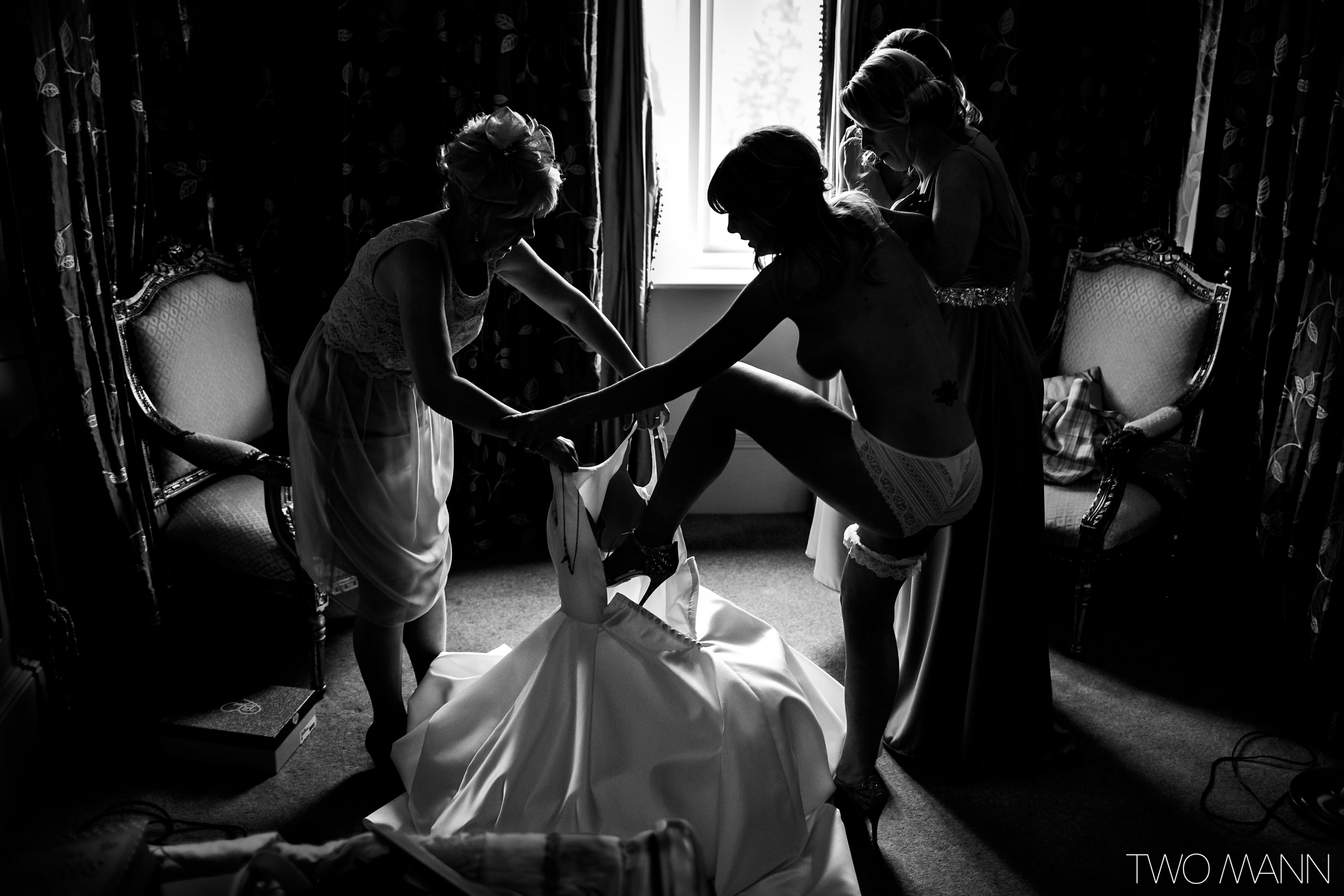 helping the bride put on her wedding dress