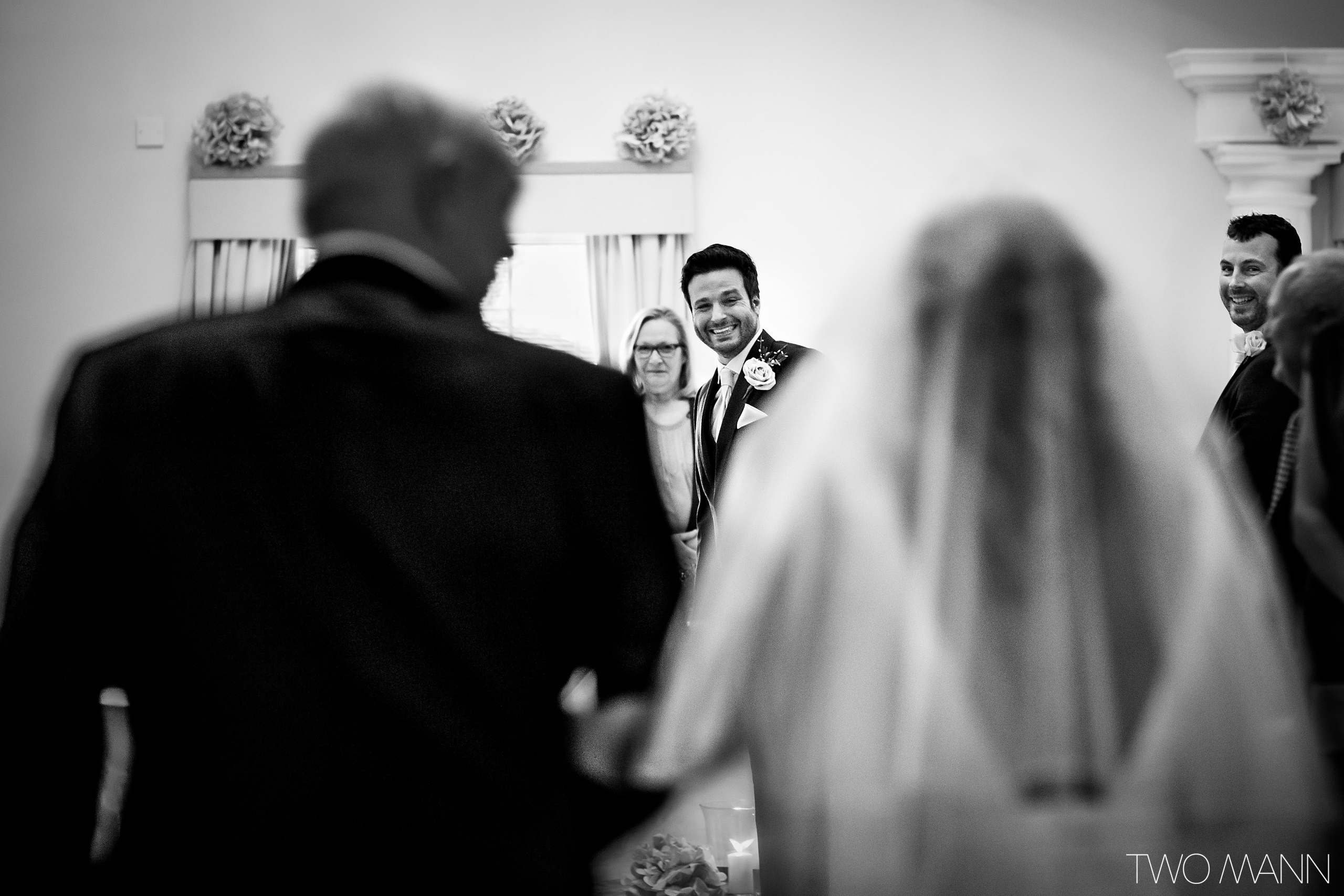 a groom waiting for bride walking down the aisle with her father