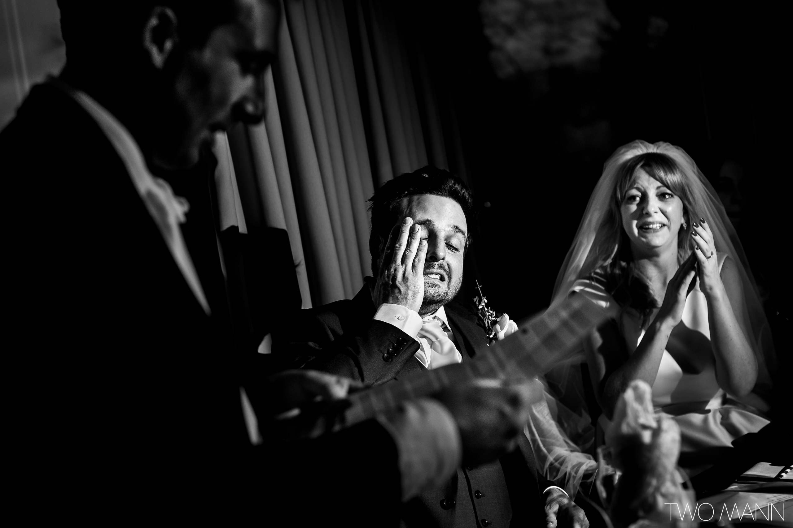 emotional groom and bride listening to a guest's speech at reception