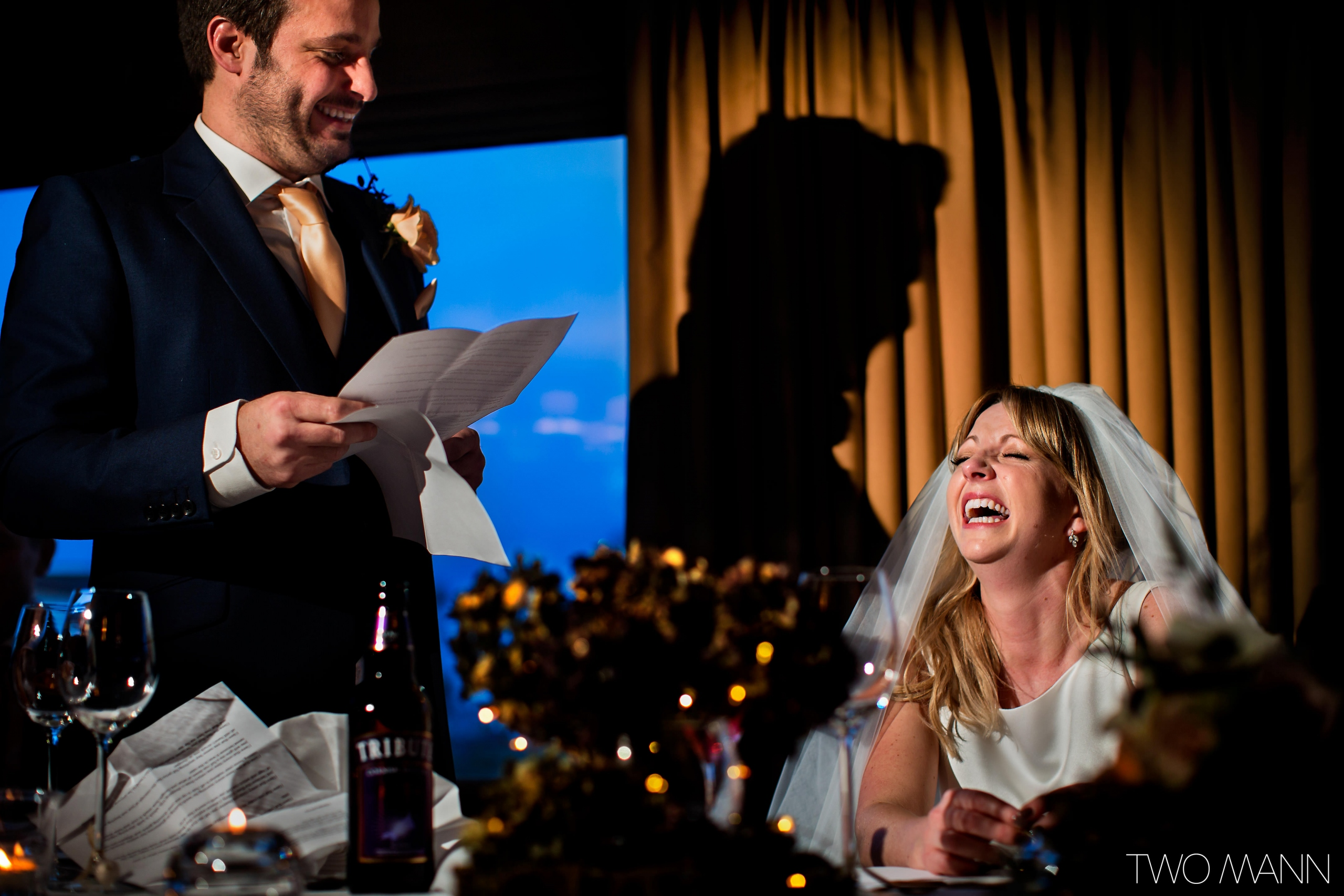 a bride bursts out laughing at groom's speech at reception
