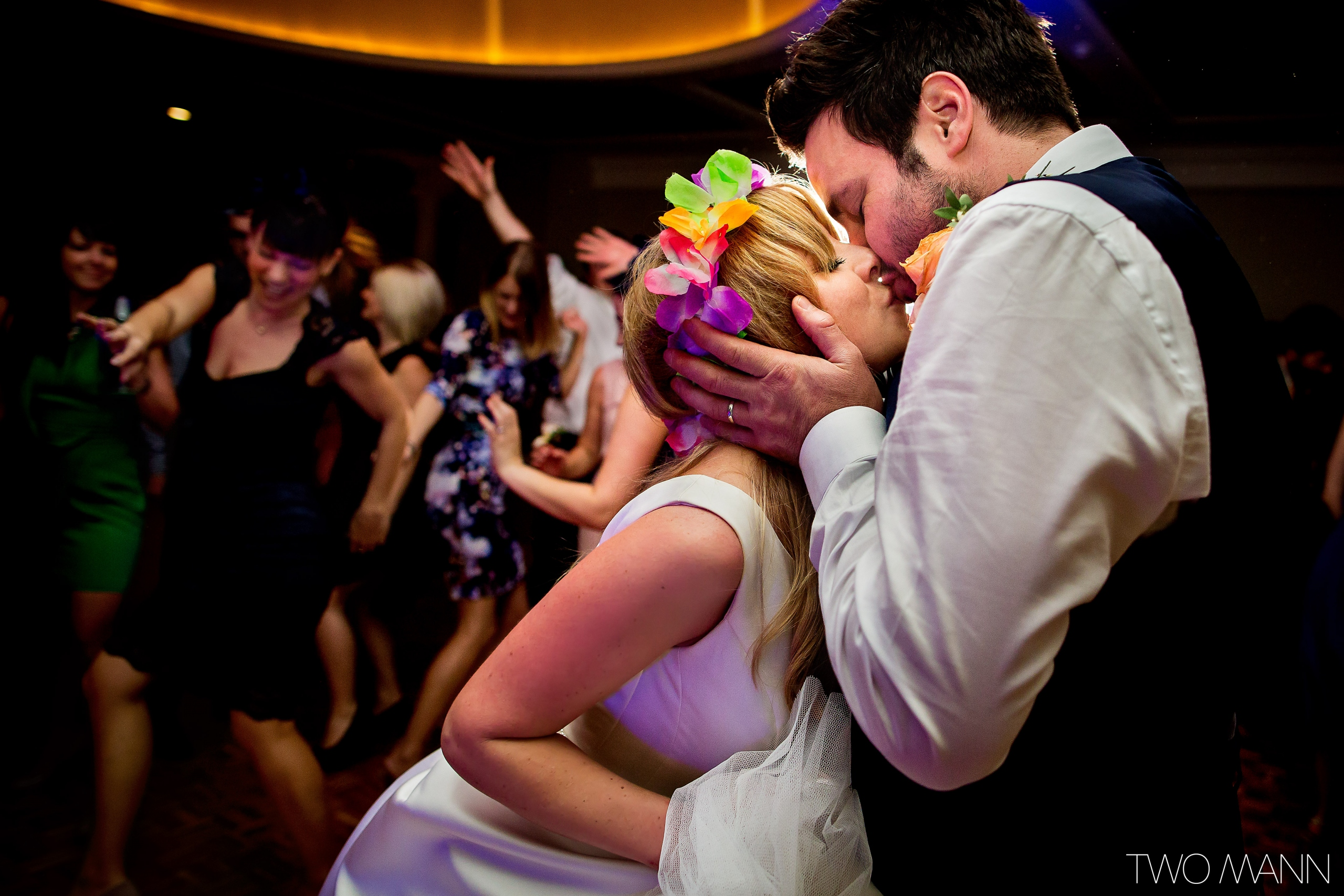 bride and groom kissing each other while dancing