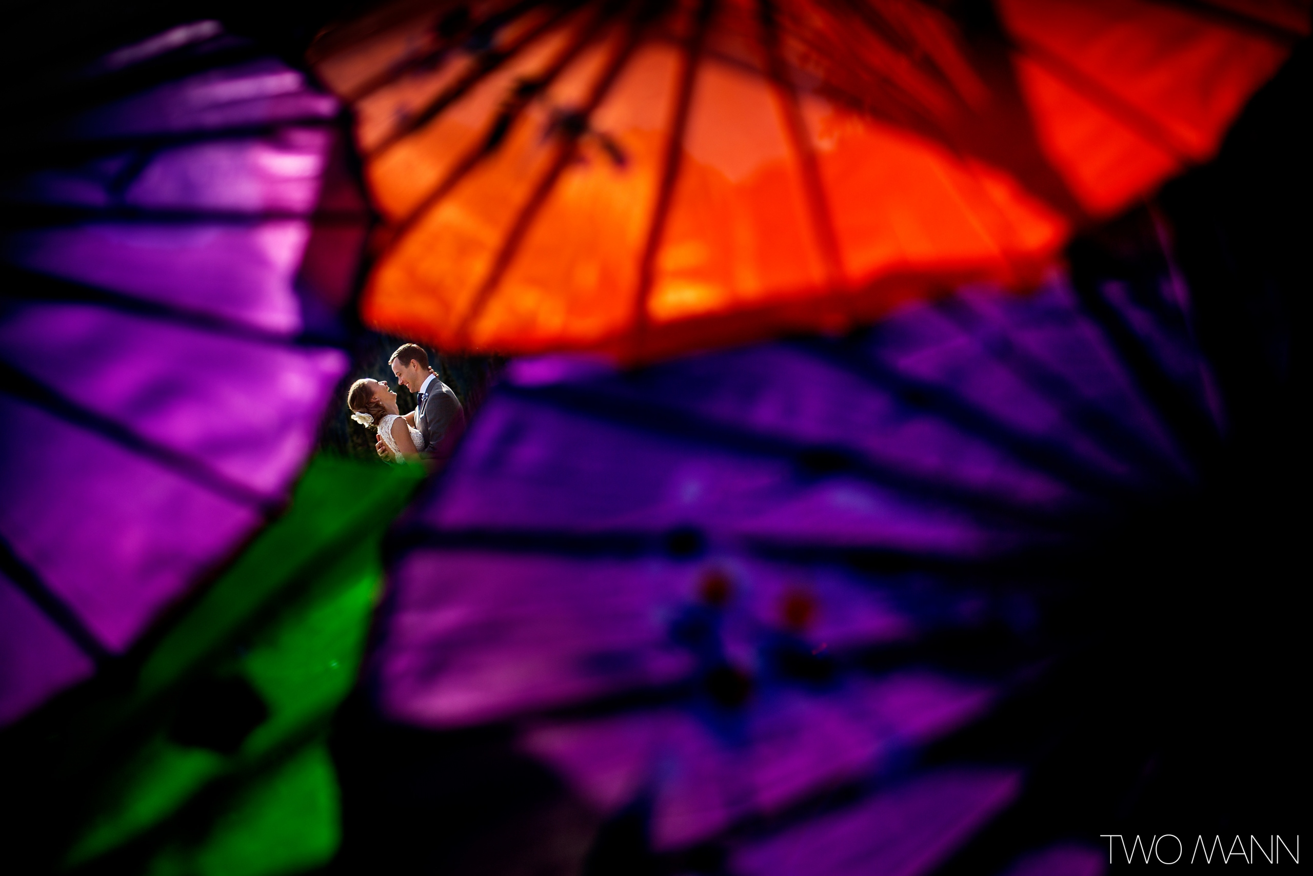Groom embracing his bride with colorful parasols in the foreground