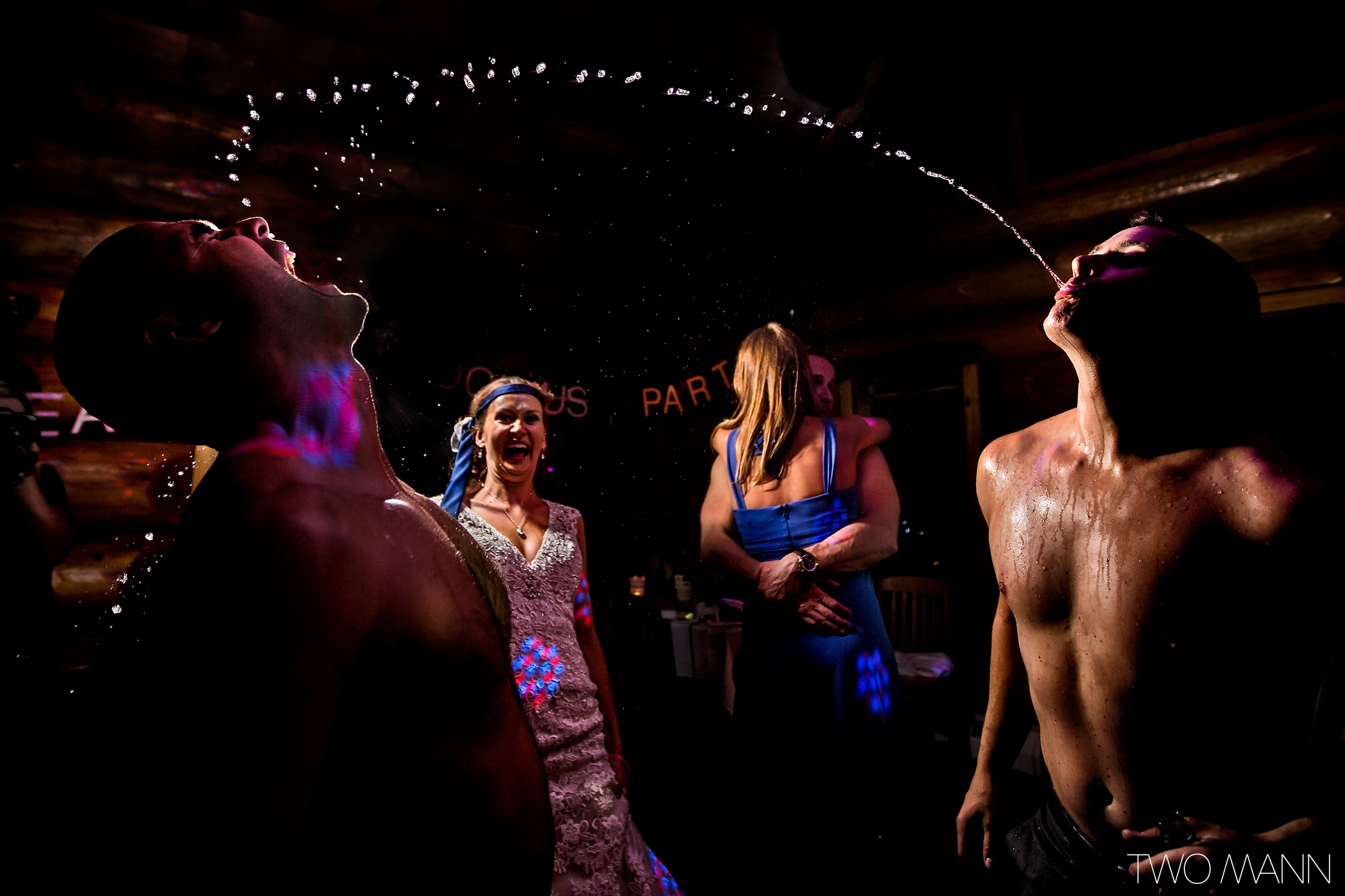 a man spraying water from the mouth at a wedding reception